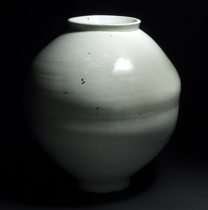 THE FORM - The traditional Korean moon jar originated during the Joseon Dynasty. Crafted by inverting and attaching two equally sized bowls, a telltale seamline often emerges during the firing. As tall as it is wide, with a restricted opening and no lid, its function has been heavily debated. Moon jars characteristically feature lunar details like a milky white glaze and rotund form.Only twenty original moon jars from the Joseon Dynasty remain in the world.