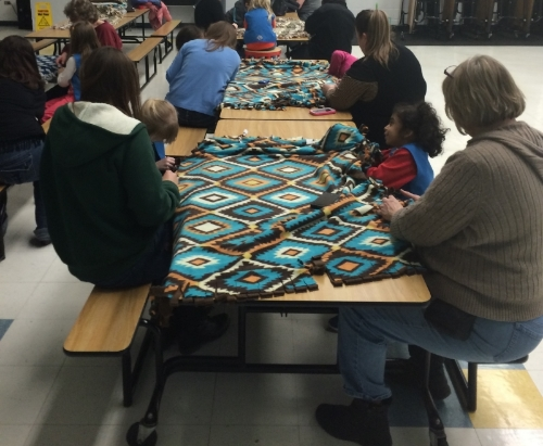 Here is a picture from last year when we made tie blankets for homeless Vets! Can you tell the girls love helping others!