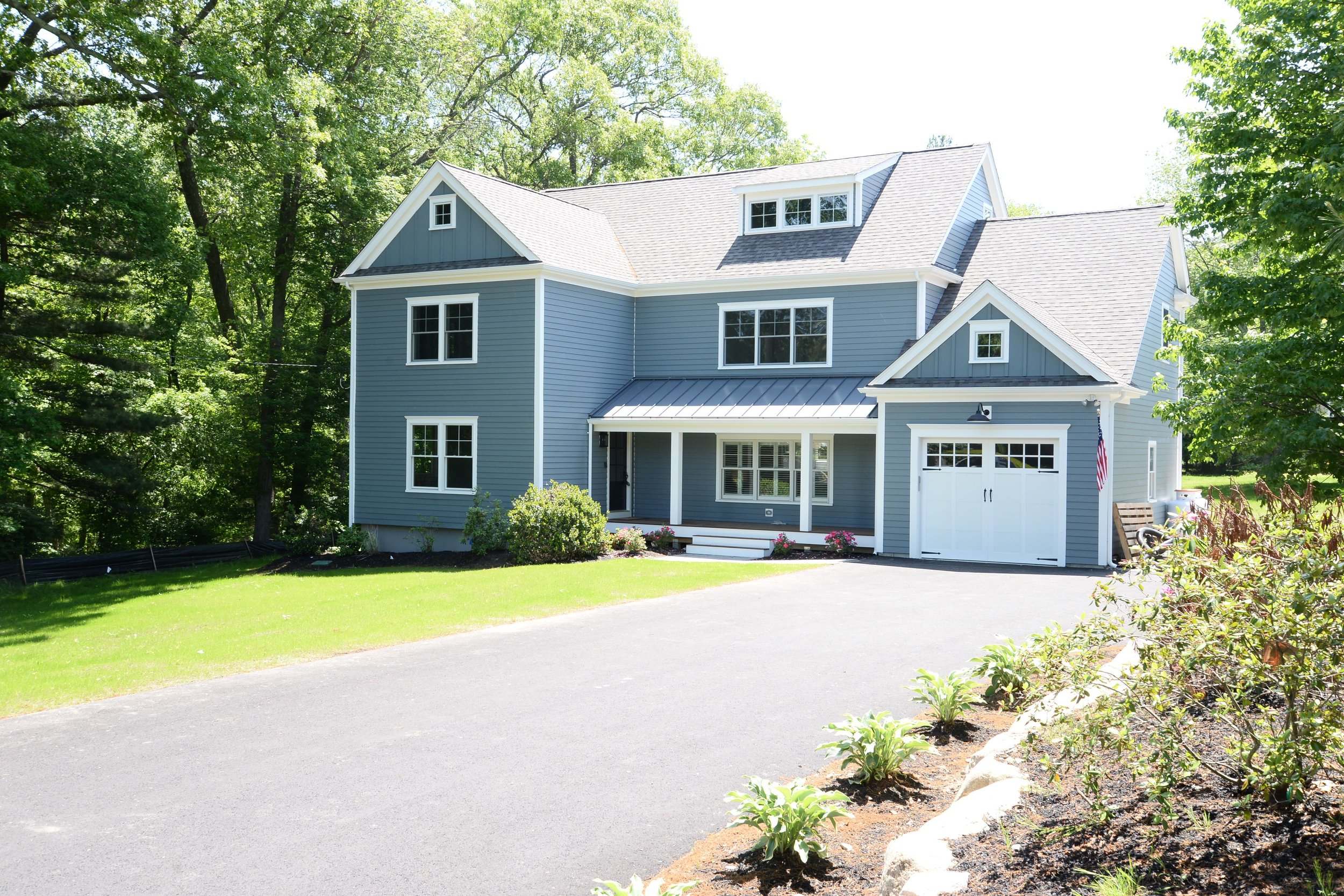 A standing metal roof, farmers porch, and custom garage door will detail the curb appeal of this offering.