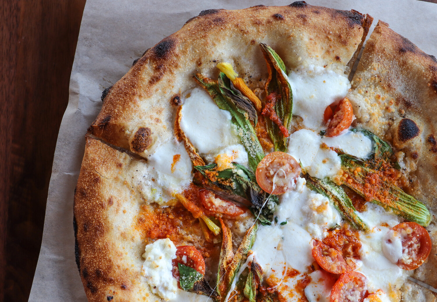 Fresh out the oven! Neapolitan inspired pizza with squash blossoms, heirloom tomatoes, Calabrian chilis, and smoked ricotta.
