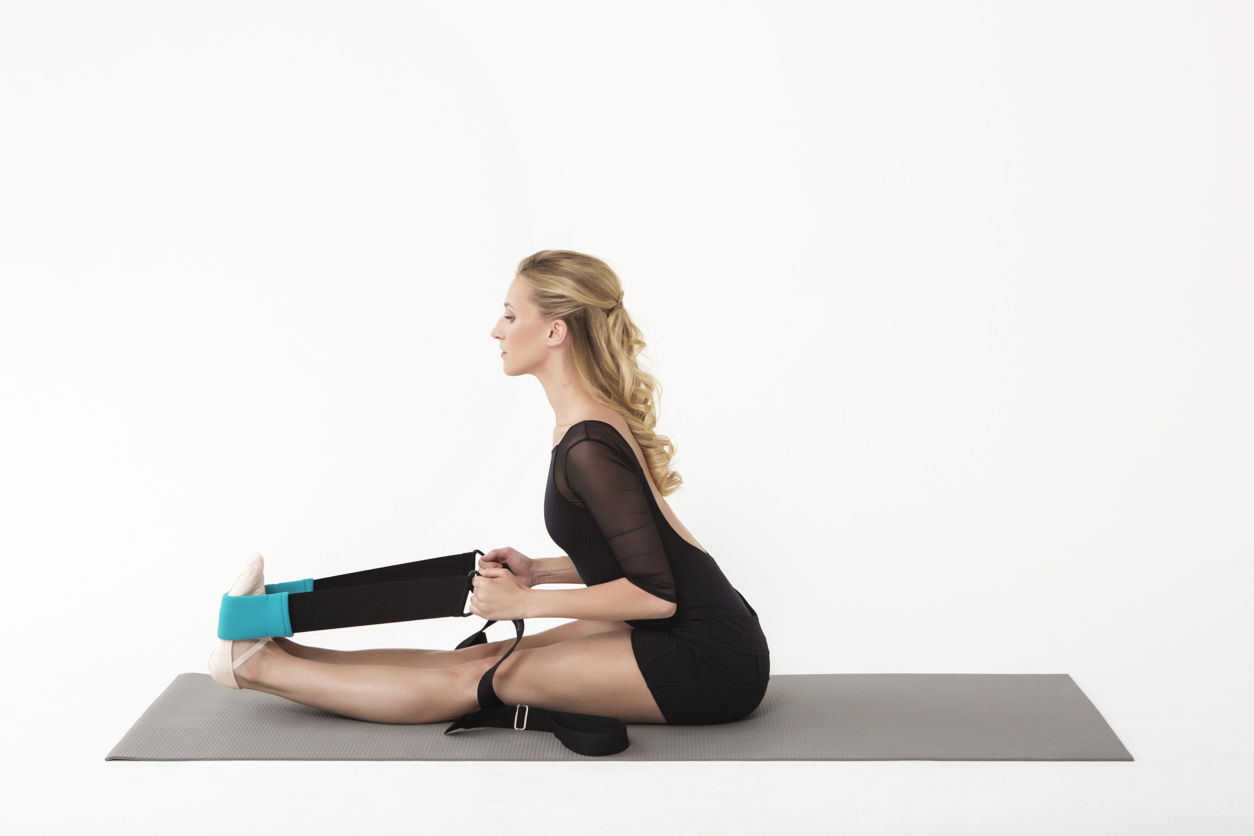Go deeper into your Paschimottanasan:  while practicing a seated forward fold, place the center strap around the soles of your feel and grab the loops in each hand. Pull the straps towards you with your elbows hugged in close by your sides as you fold forward. Press through the soles of your feel as you pull yourself forward to achieve a greater stretch.