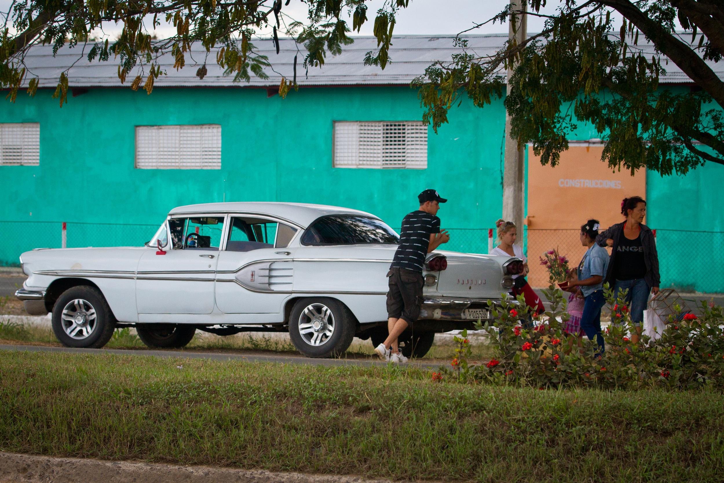 Locals hanging out by their classic American chrome, Ciego de Avila, Cuba