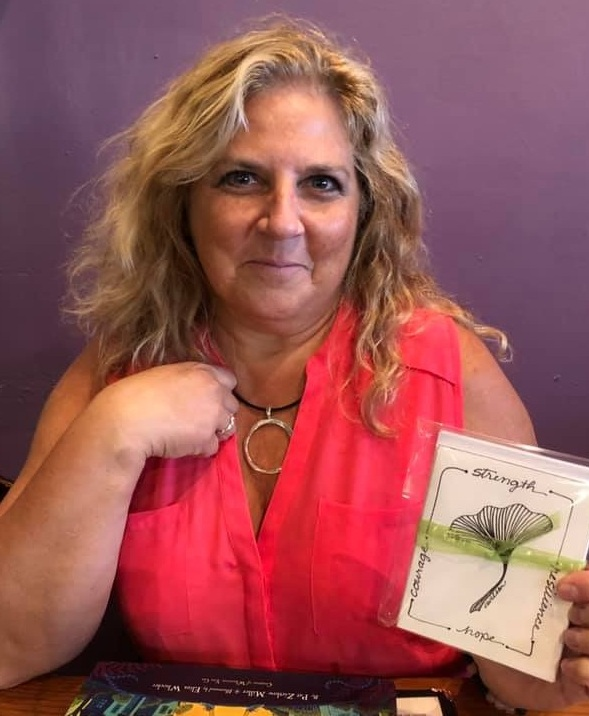 Christine Wilson holding the Ginkgo Leaf Gift Cards she created for COIPP.