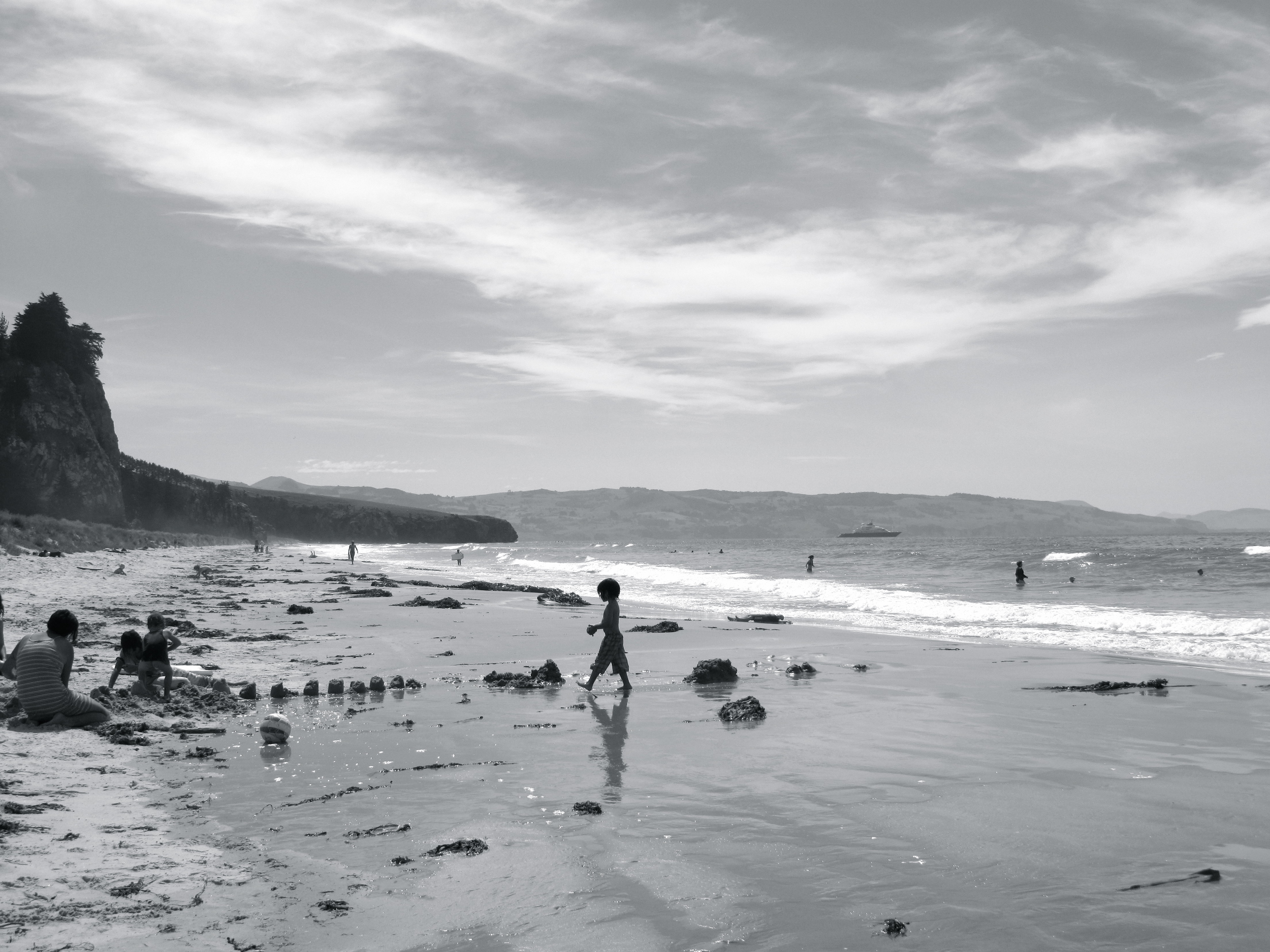 kid making sandcastles at the beach - black and white art photo