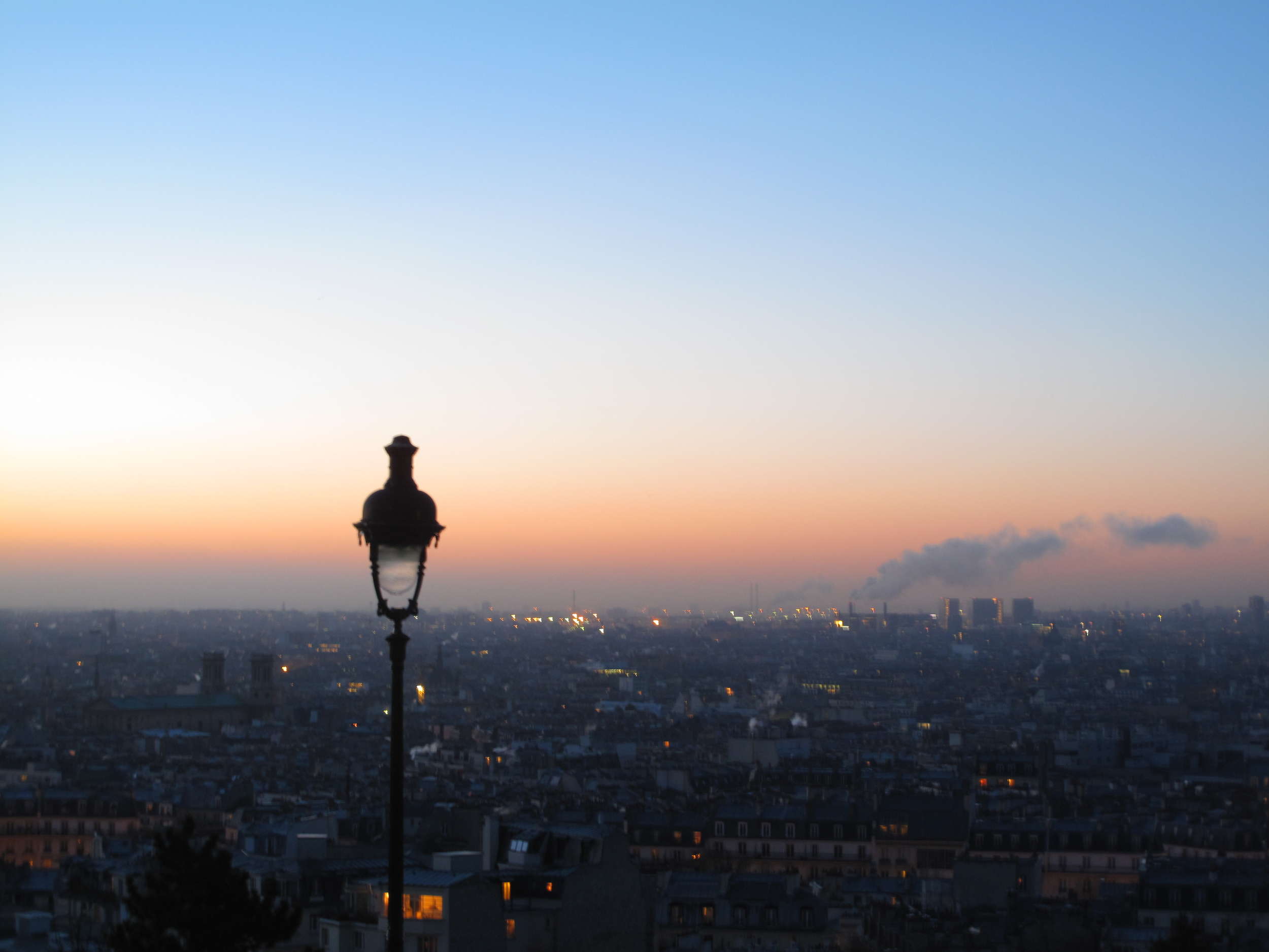 Sunrise over the city of Paris, lamps still lit in a dusky pink dawn