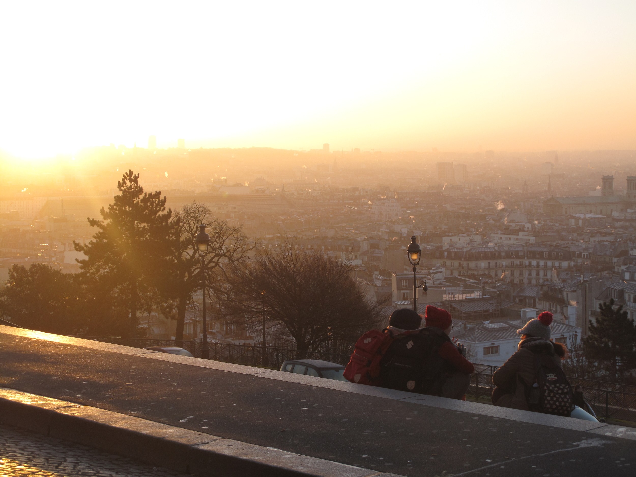 Three friends watch the sunrise over Paris from Montmartre