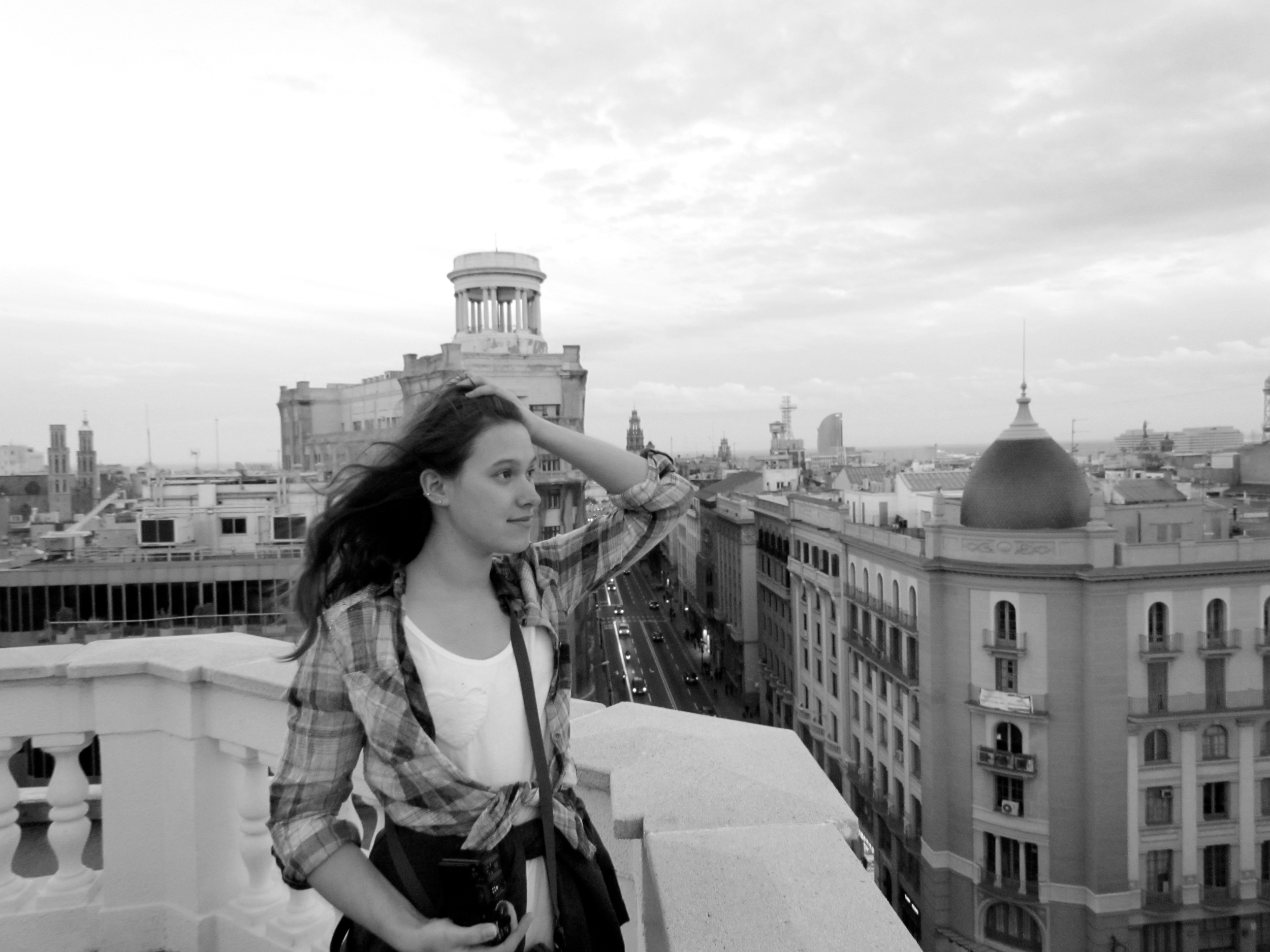 Me, Zoe, on a rooftop in Barcelona with a view of the old city