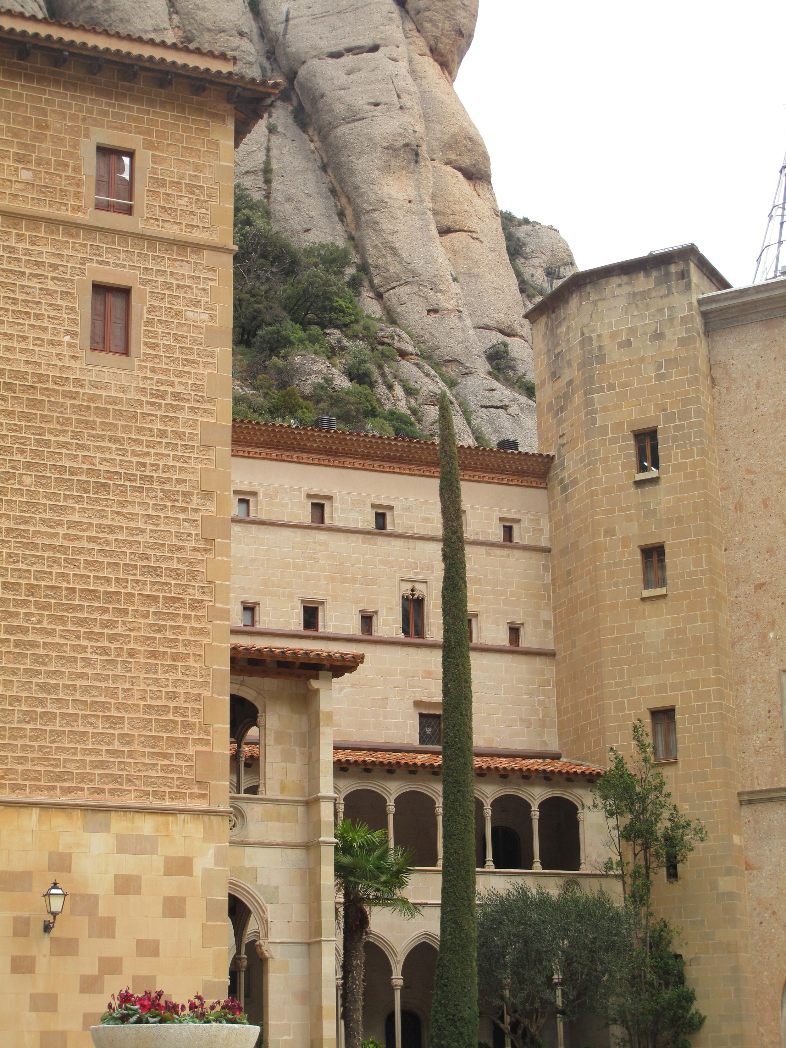 Cream stone buildings and cypress trees in the hills of Montserrat