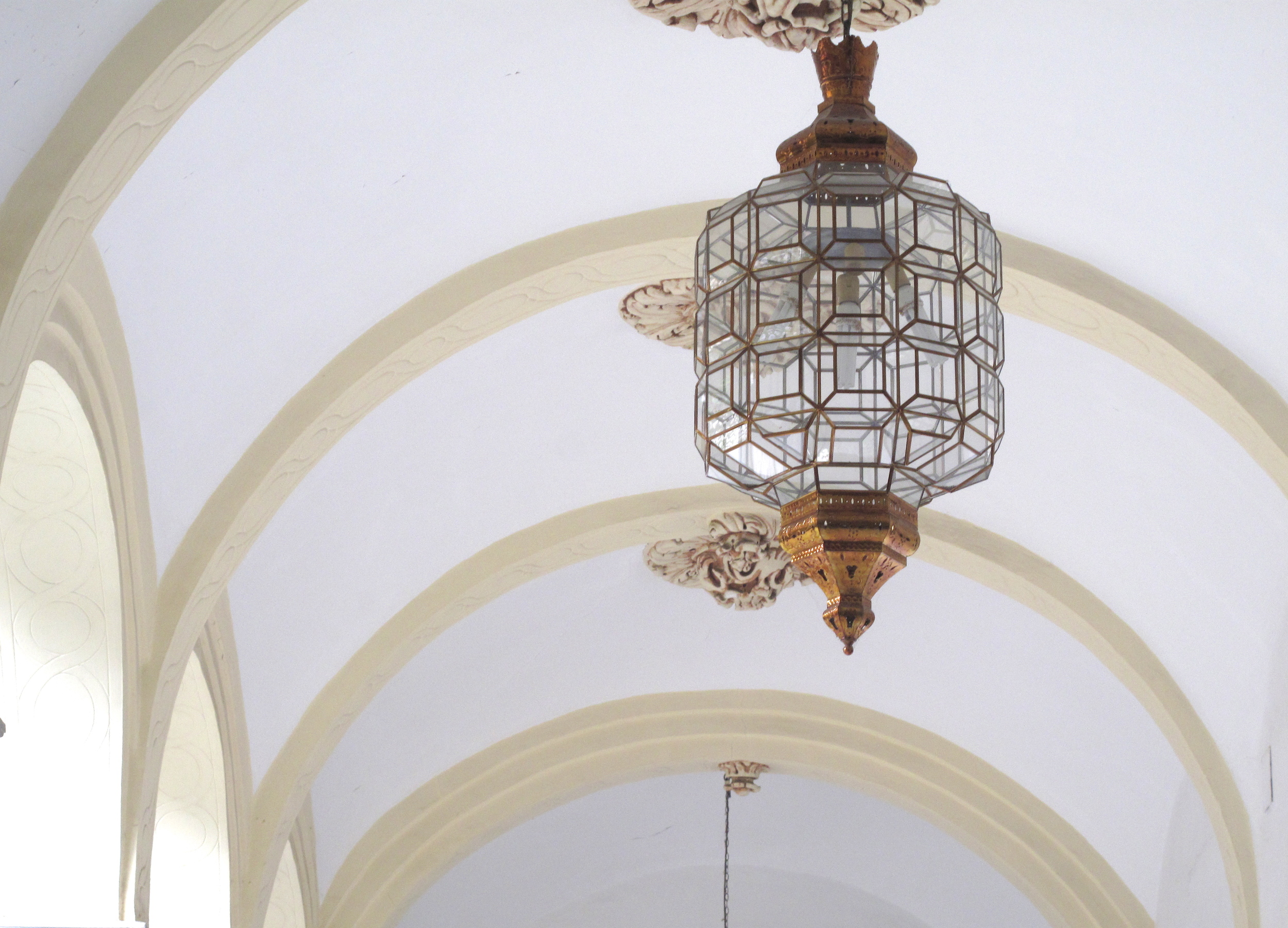 glass light shade in geometric oriental design in a white corridor
