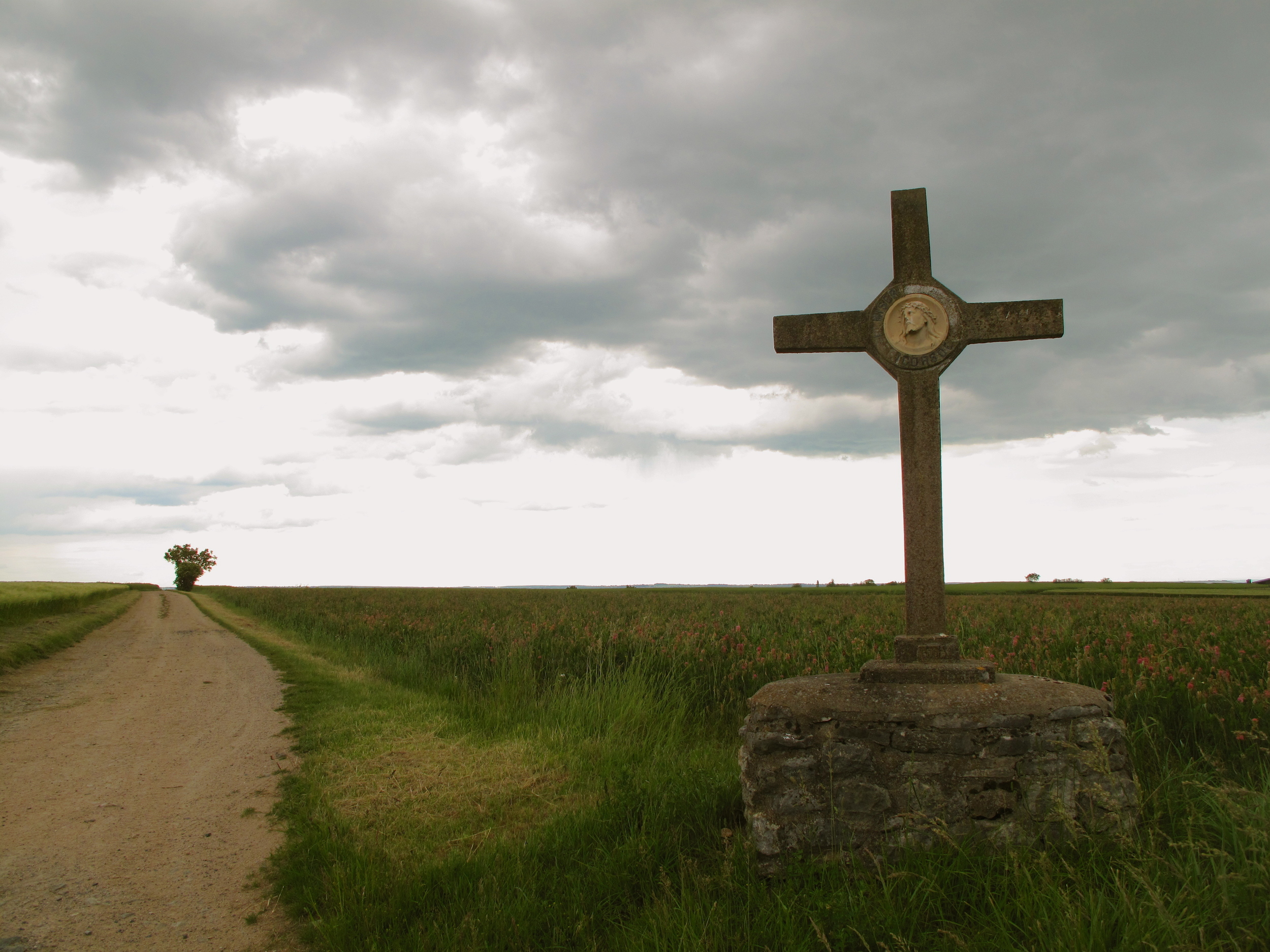 A cross on the roadside and storm clouds, Auvergne