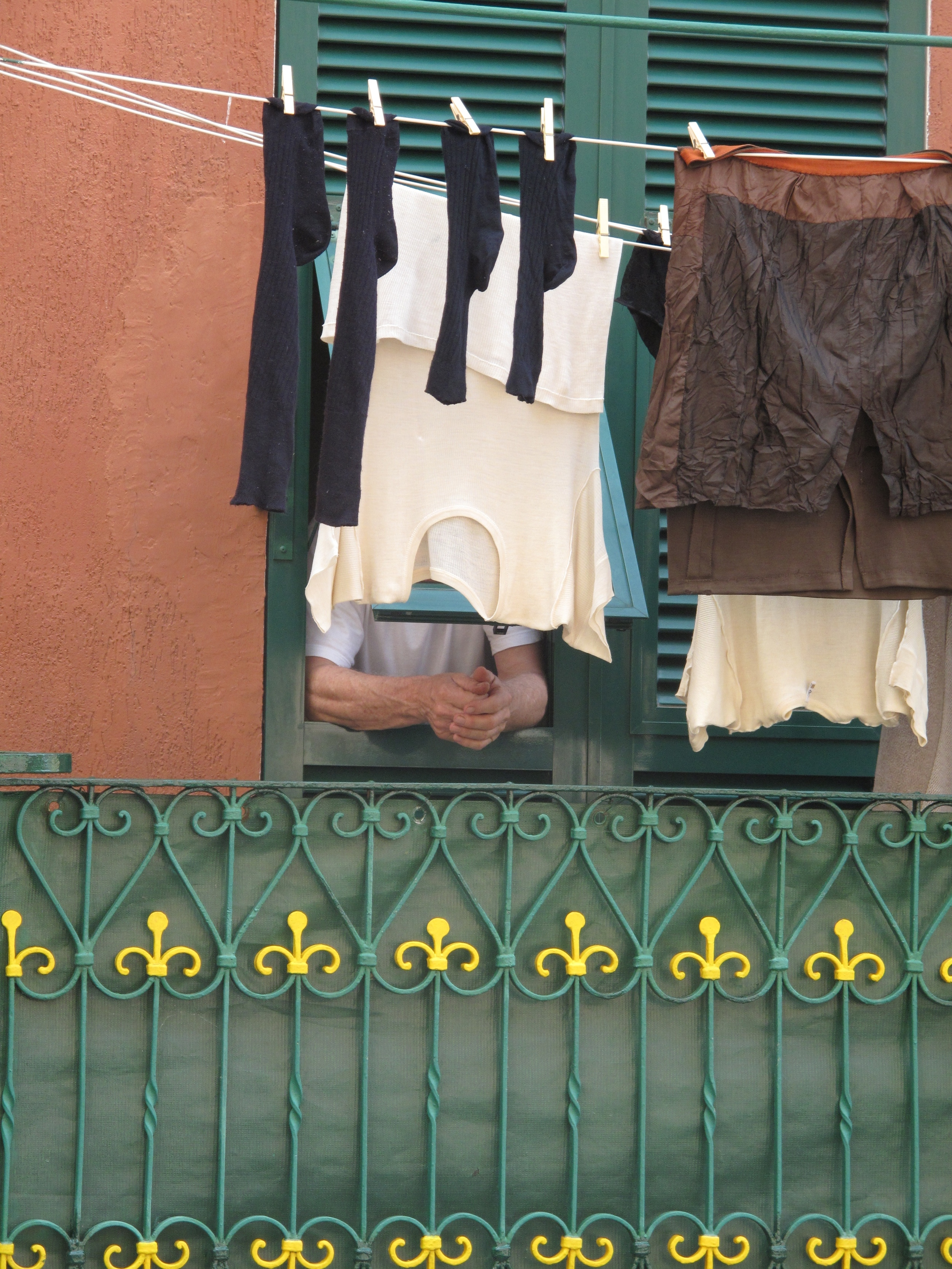 An old italian man peering out his window and watching the street behind some washing