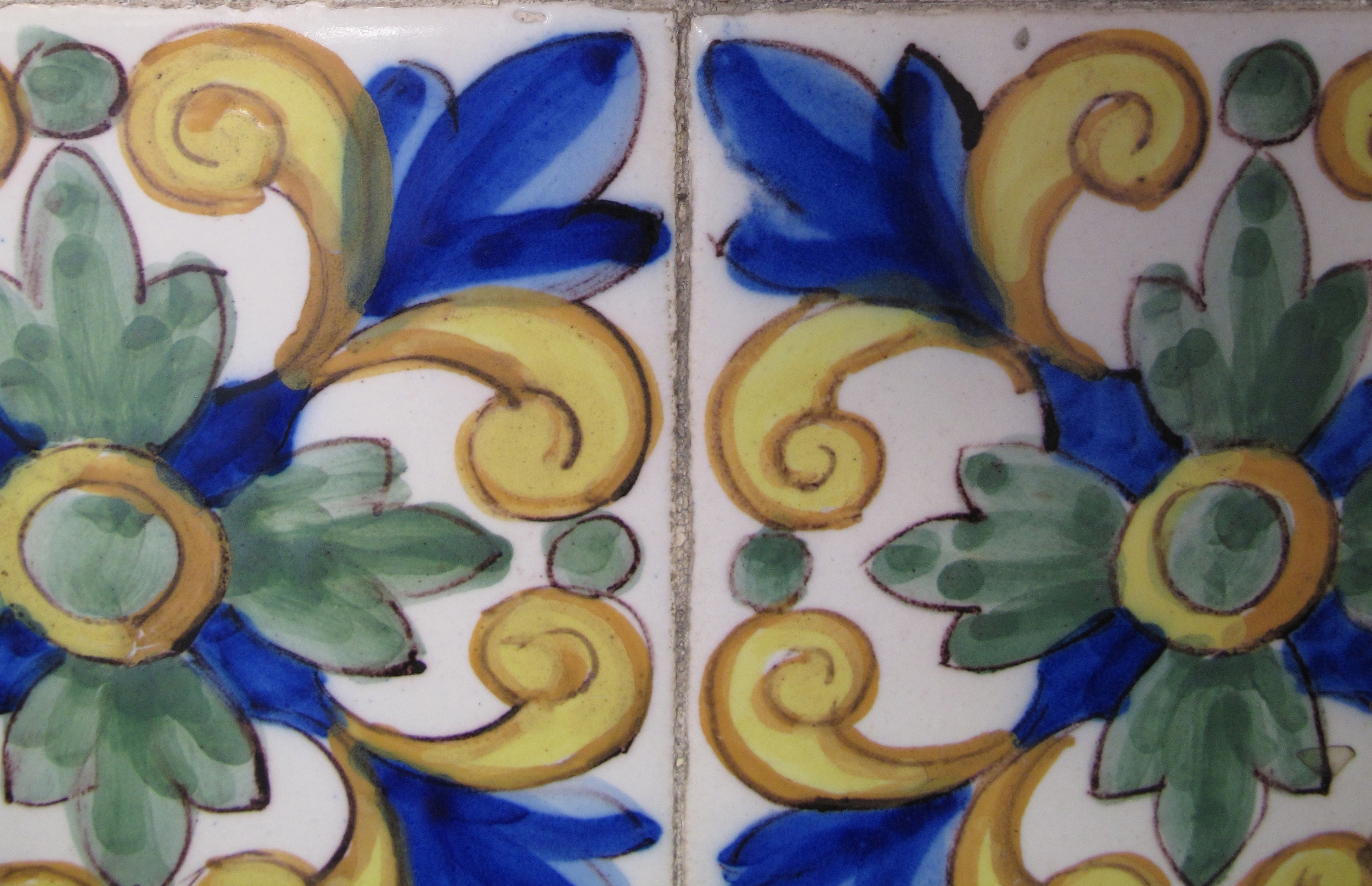 Old tiles with blue and yellow painted curlicues