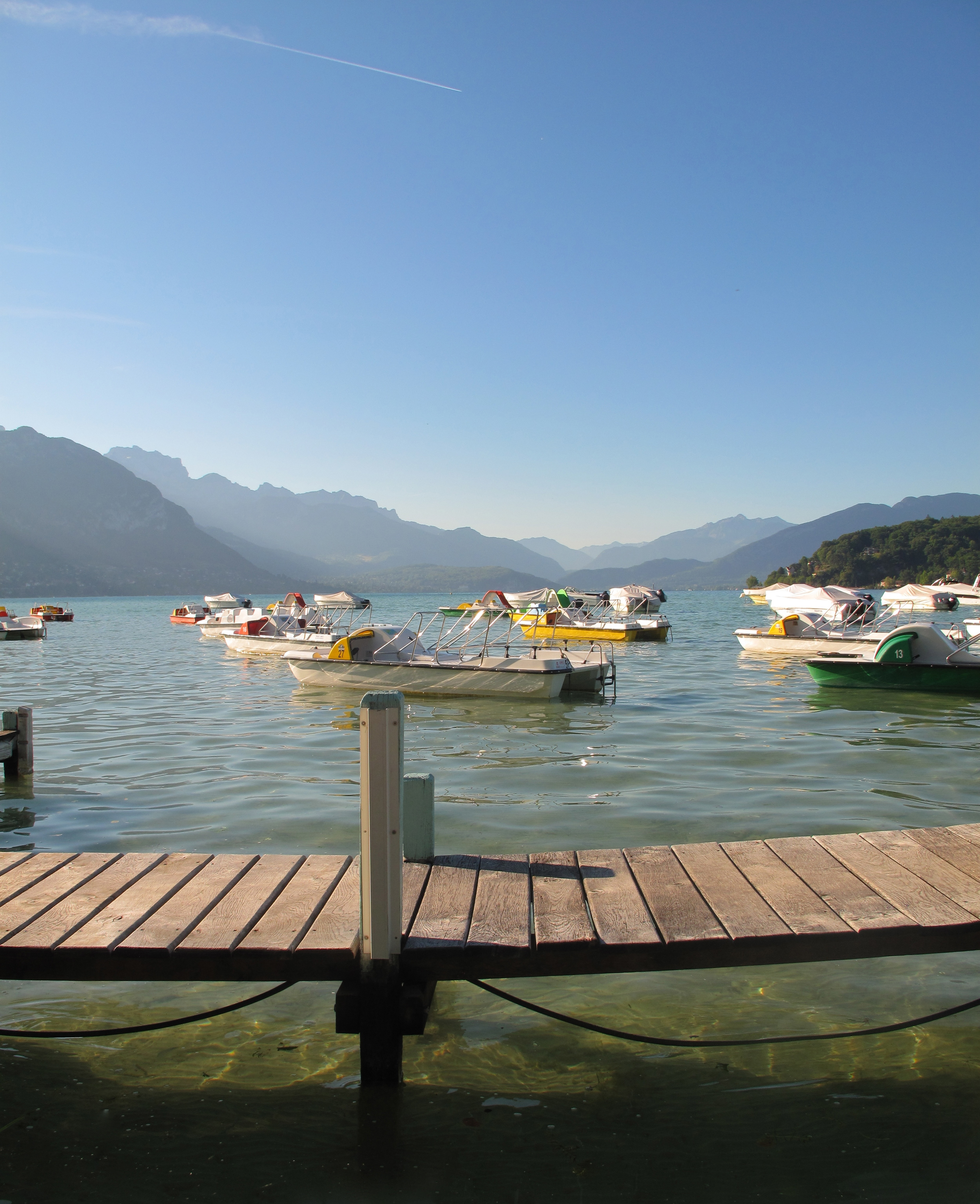 Boats on Lake Annecy in the summer - the water is completely clear and turquoise coloured