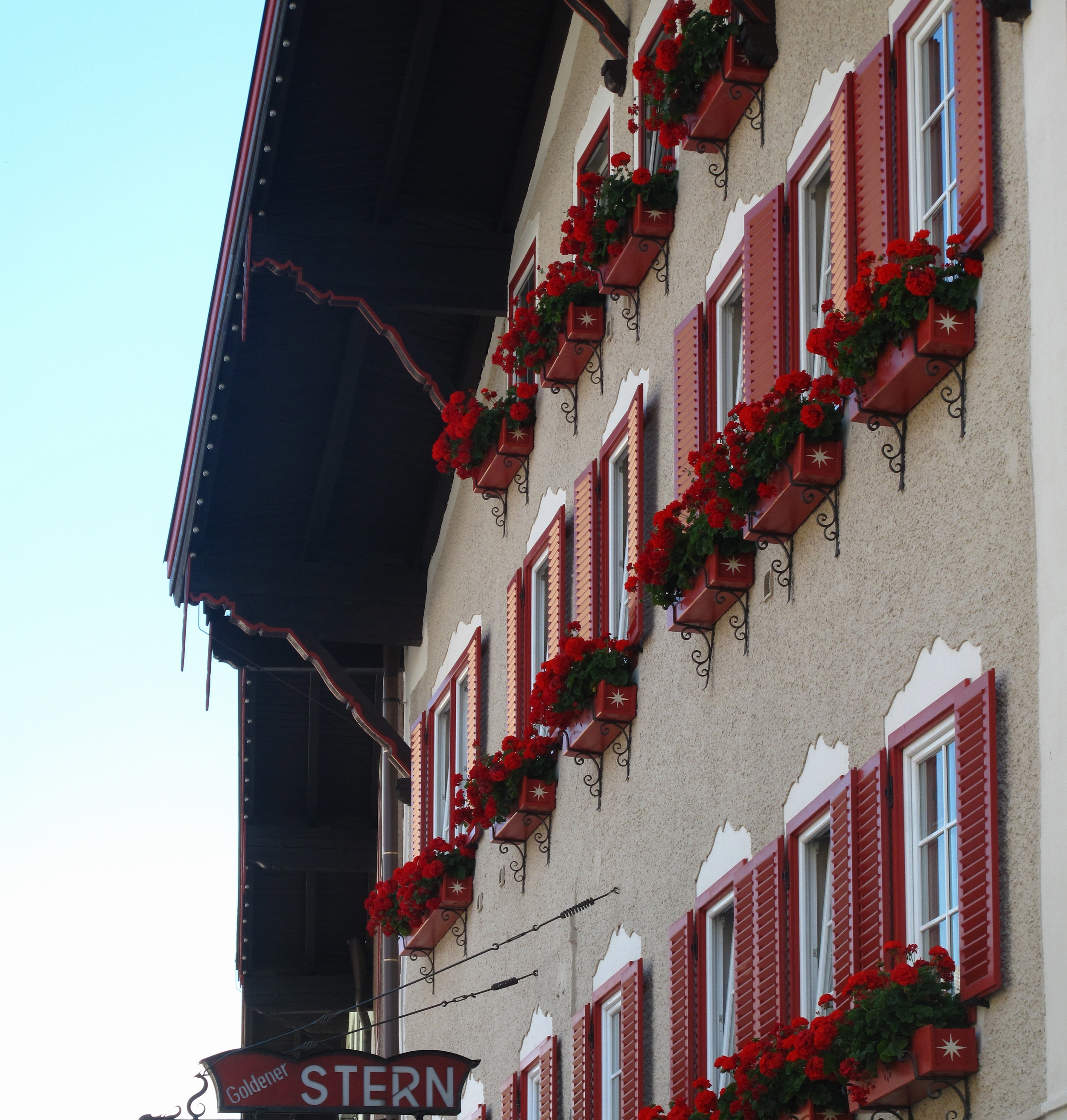 Austrian hotel with window boxes full of red flowers.