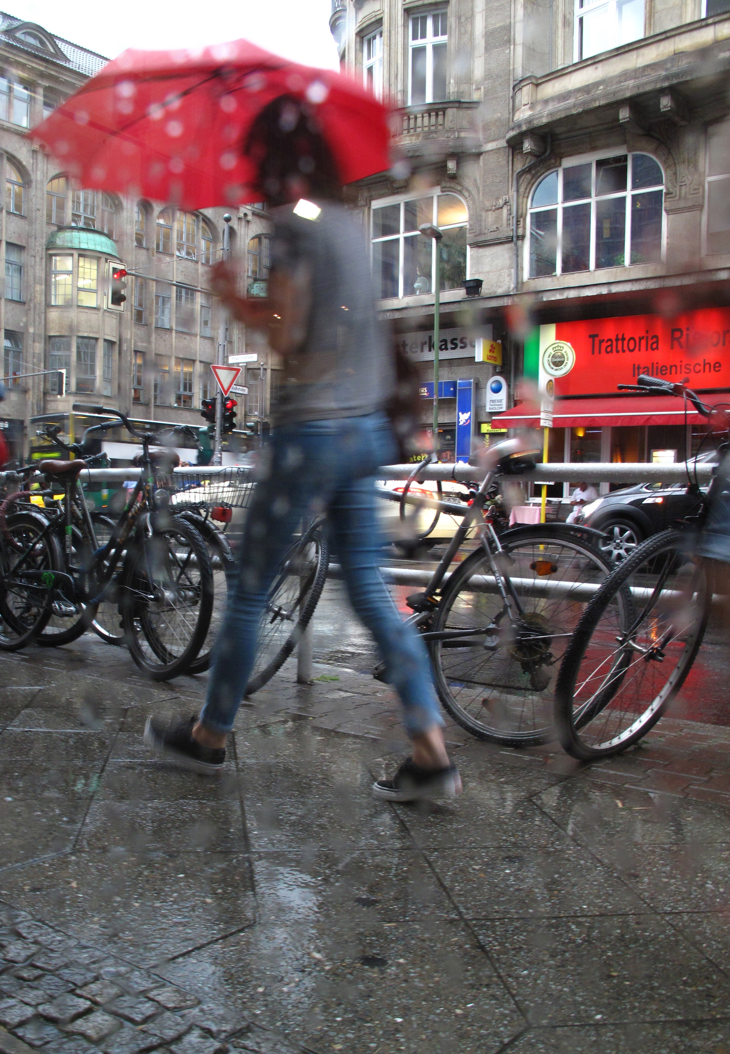 Rain on the window, and people passing with colourful umbrellas in Berlin