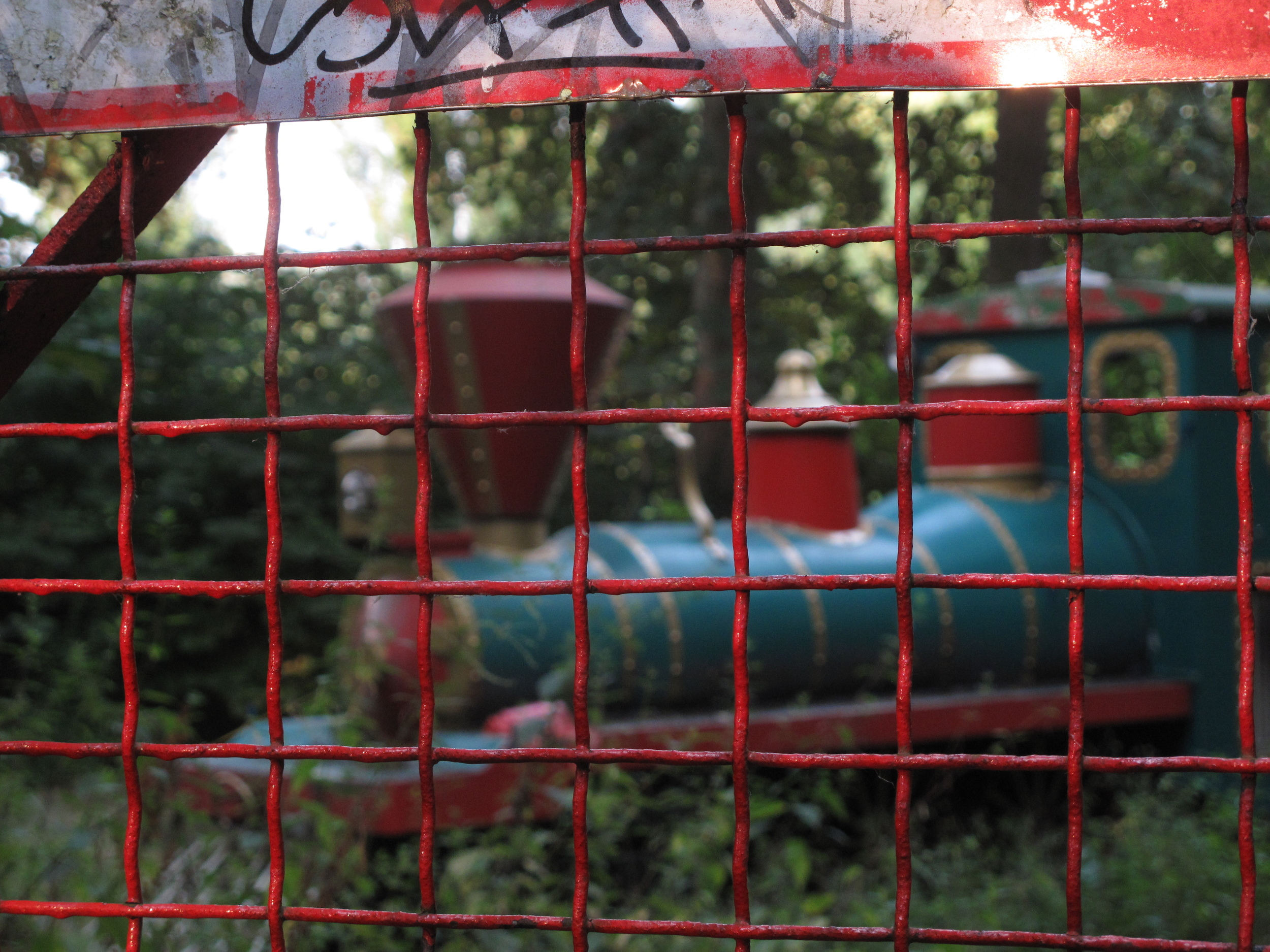 Old red and green train in Spree Park behind the fence.