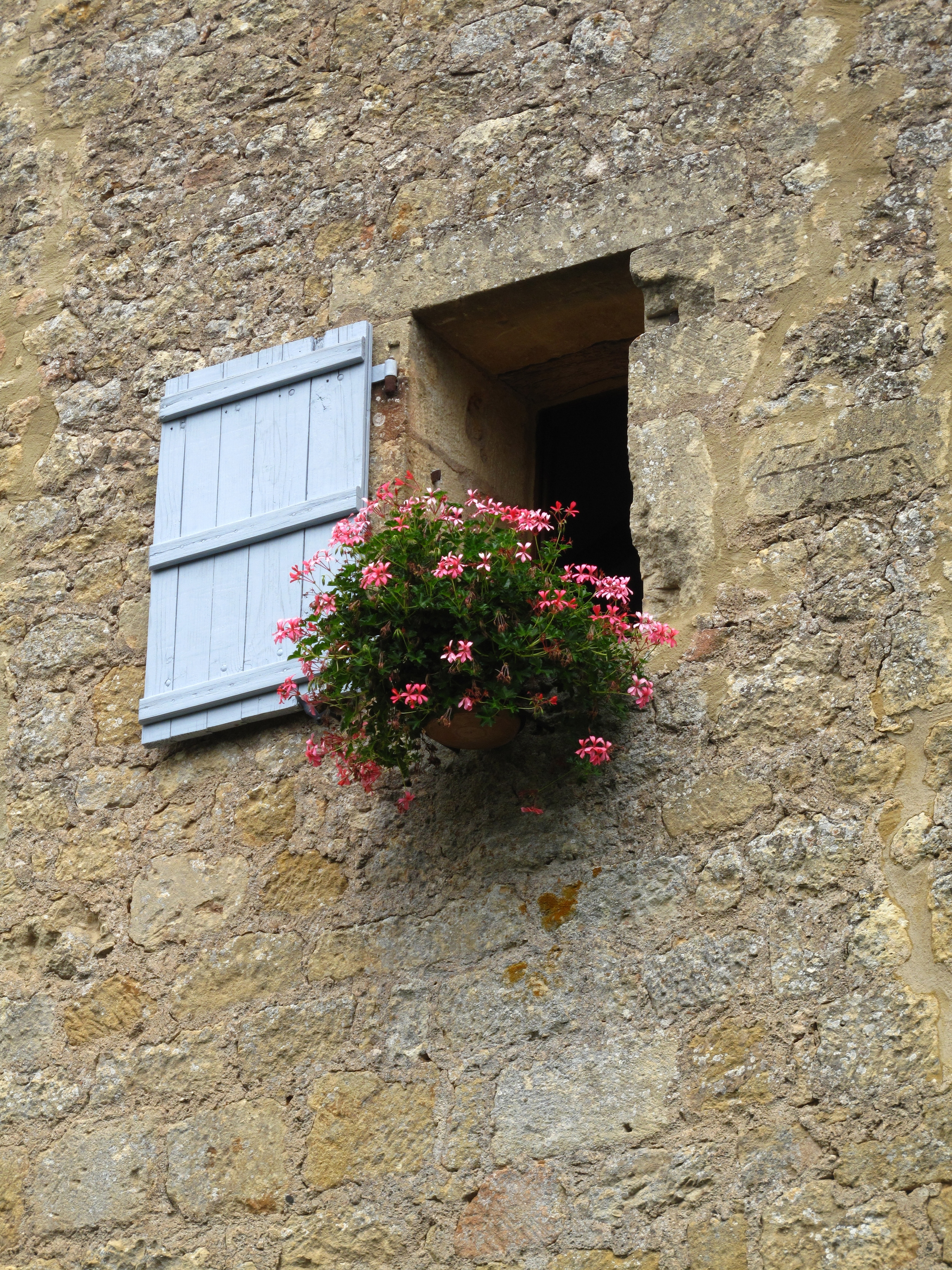Tiny window and flower box on a stone wall, Dordogne houses.