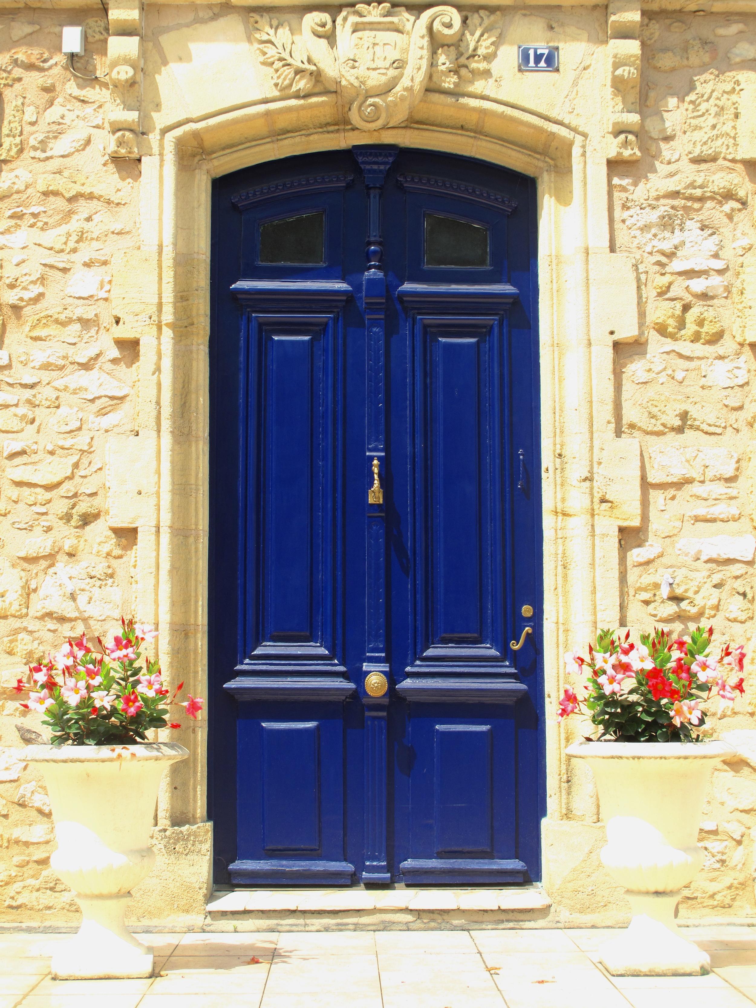Blue doorway in a stone wall, Les Eyzies de Tayac, France.