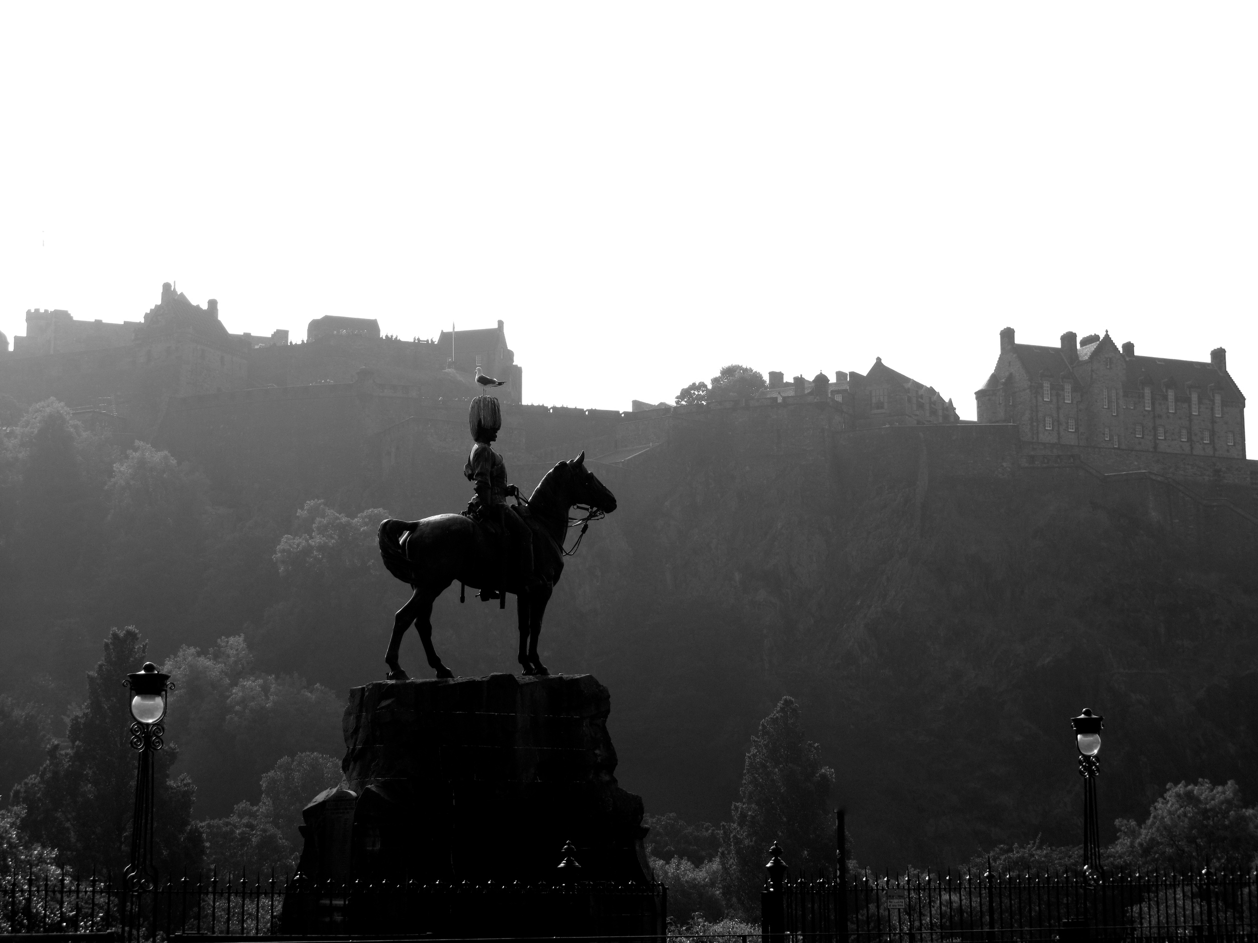 View of the castle in the morning, and an equestrian statue.