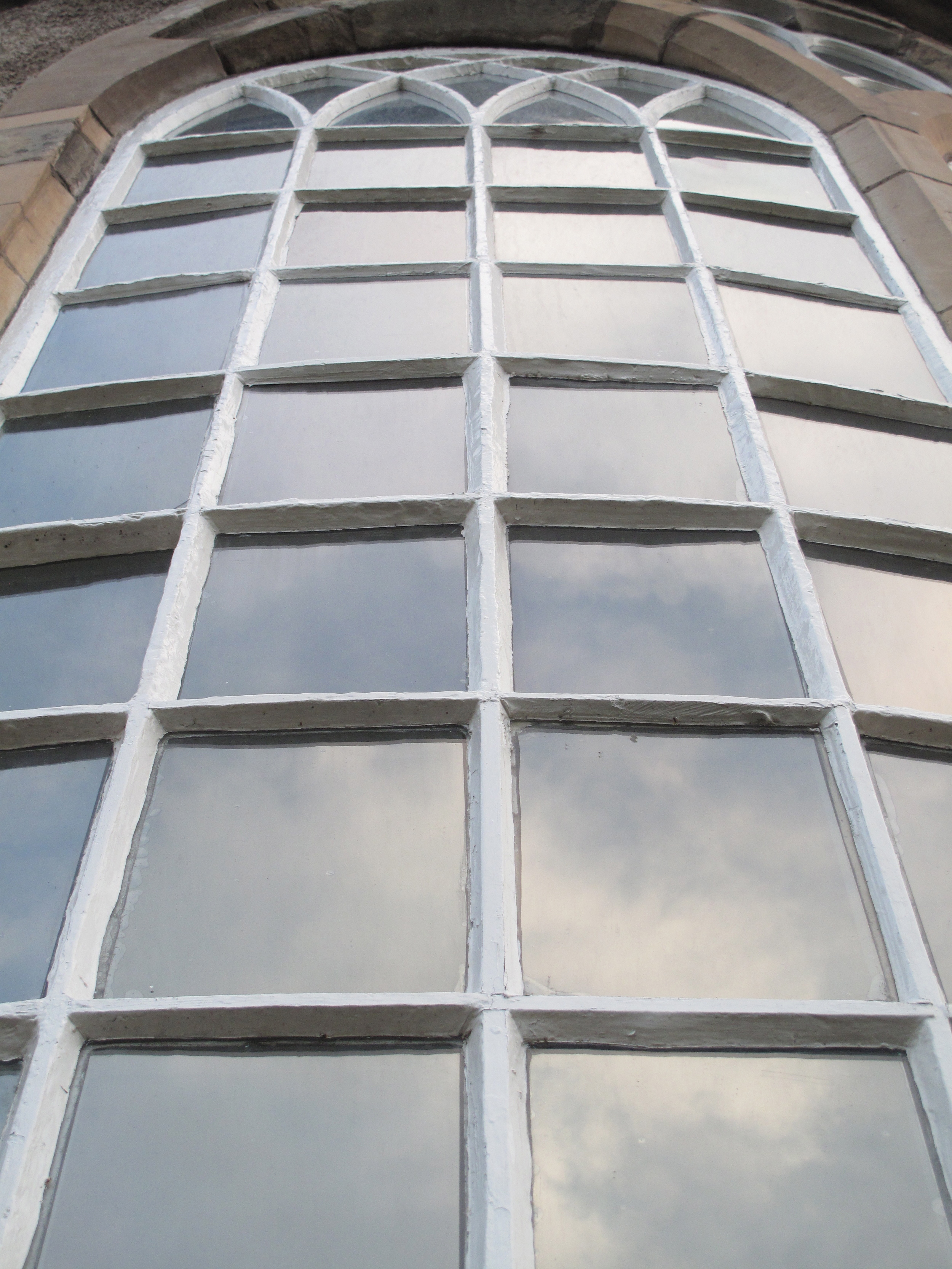 Arched window with many panes of glass, reflecting the clouds.