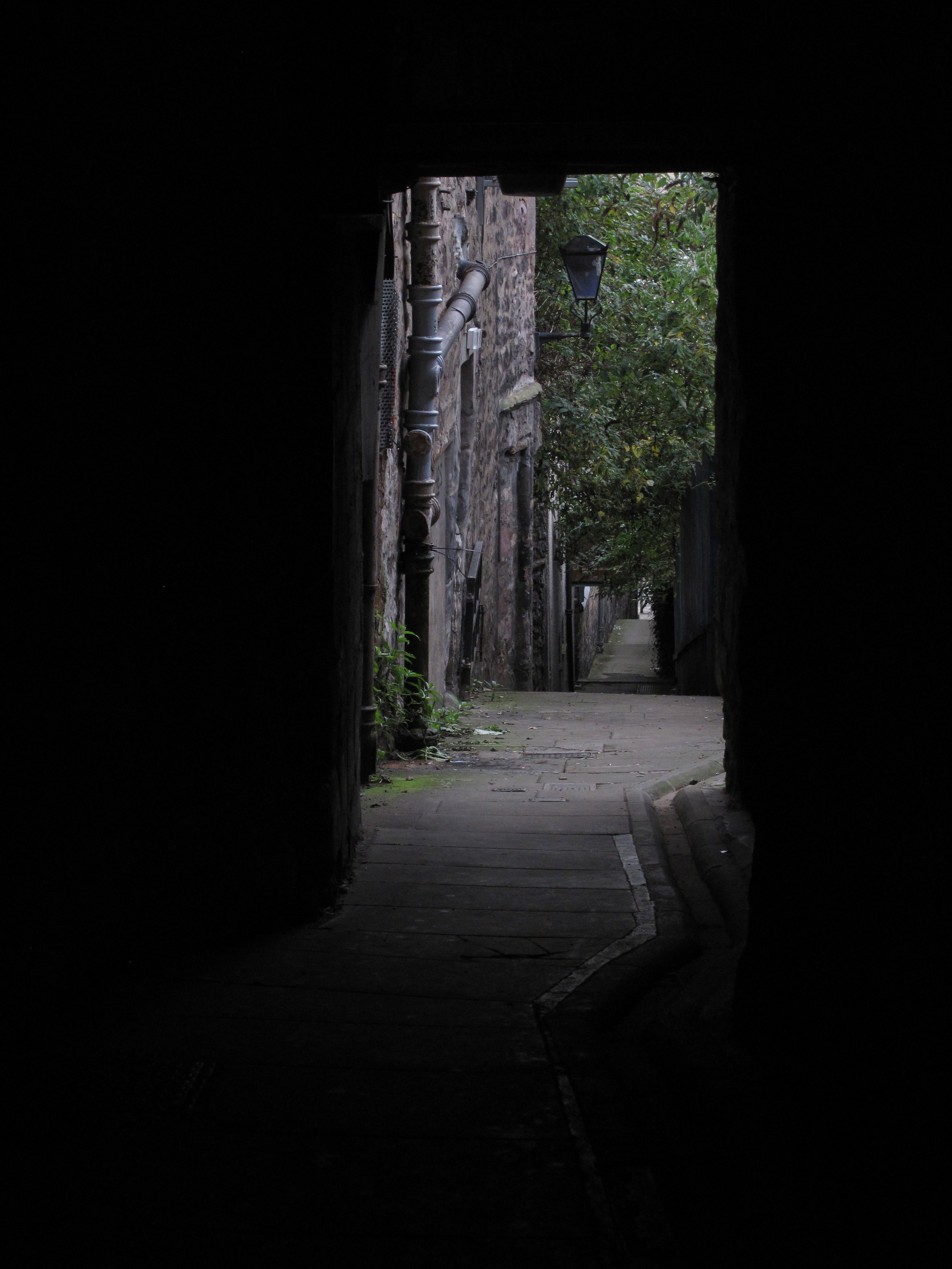 A dark close leading to a courtyard in Edinburgh's Old Town. Light at the end of alley.