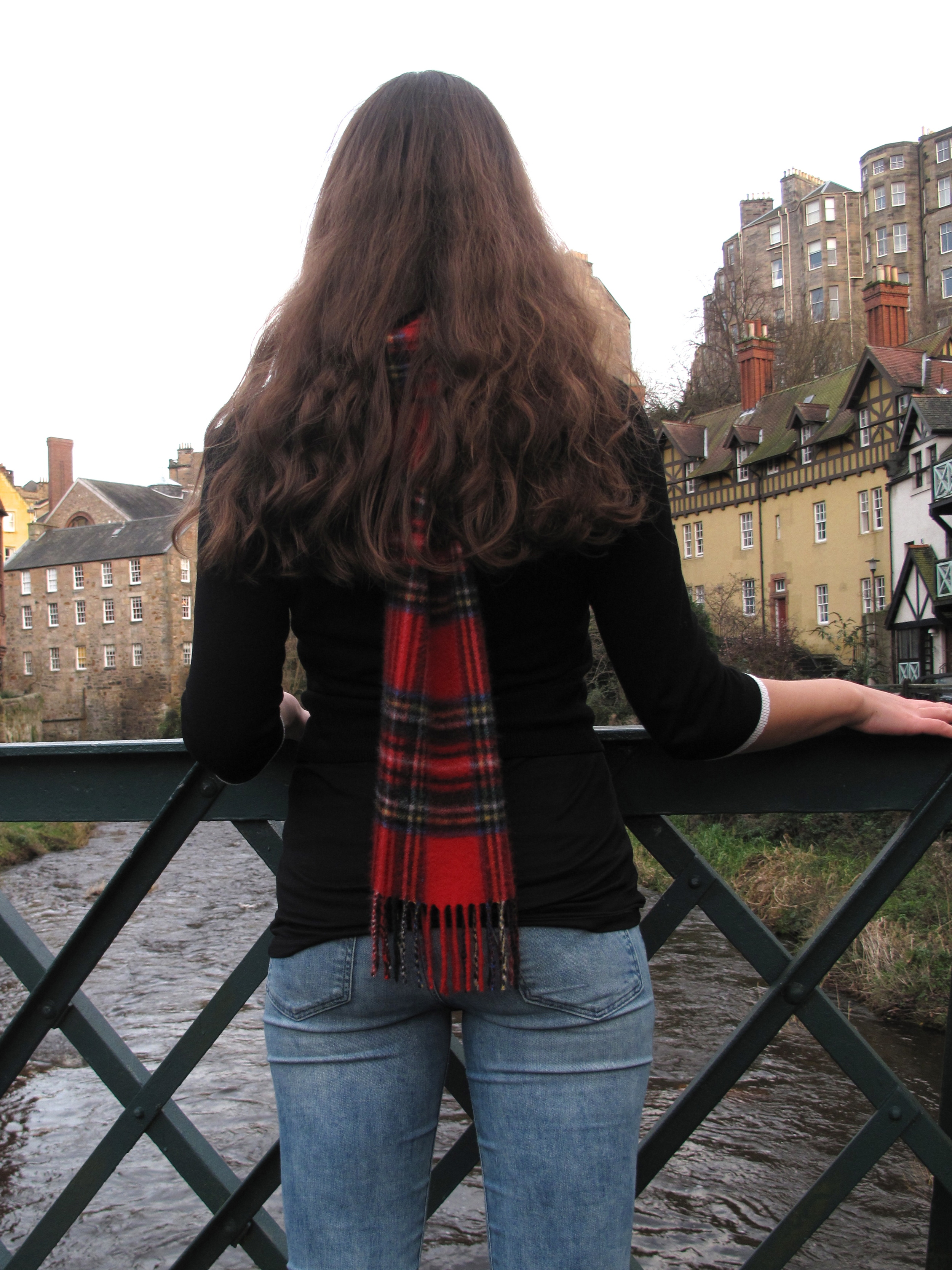 Standing on the bridge of the river in Dean Village, winter time with a scarf.