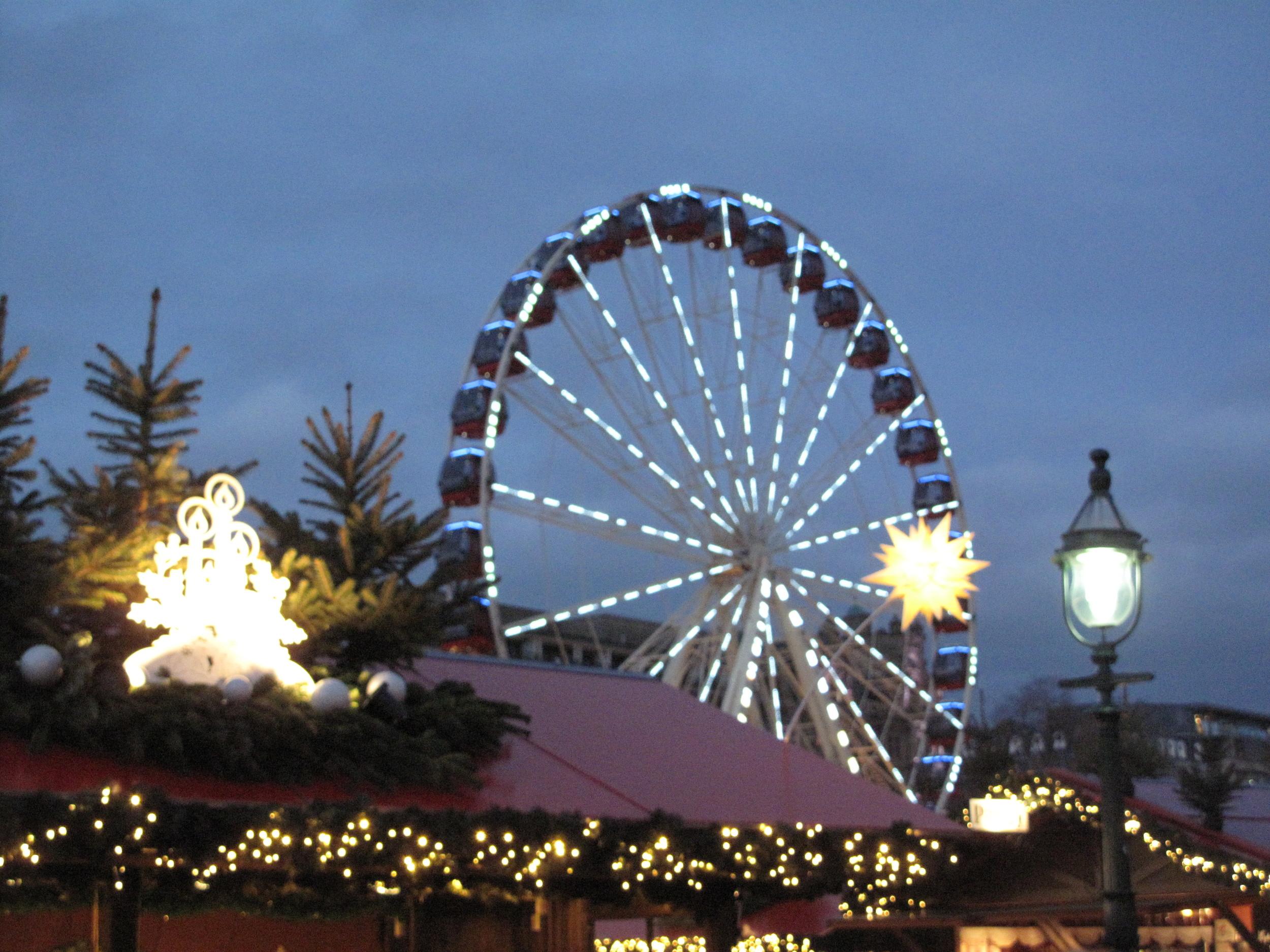 Princes Street Christmas market with the ferris wheel lit up at night time, Edinburgh.
