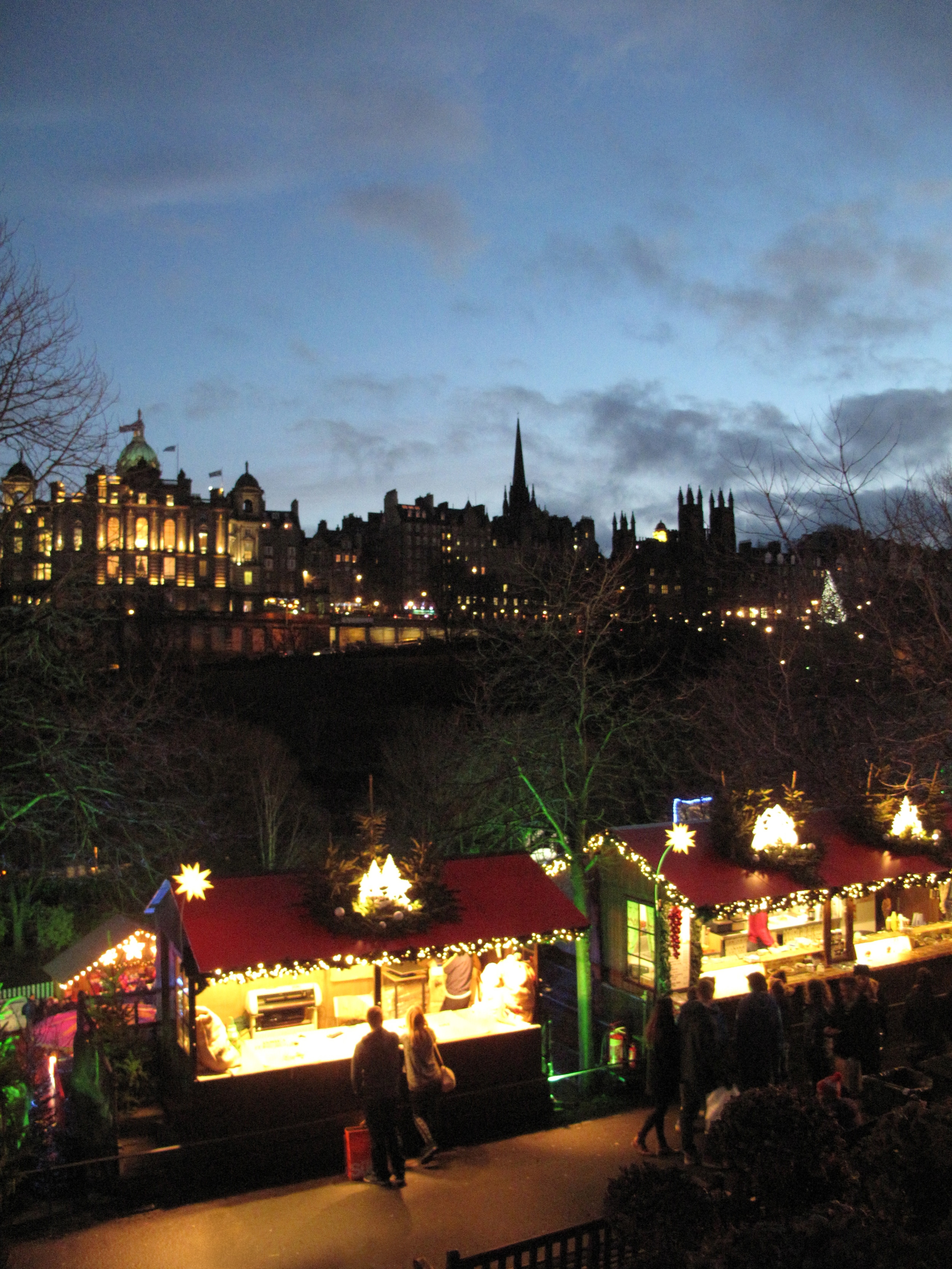 Edinburgh christmas markets in Princes Street gardens - with view of the city at night.