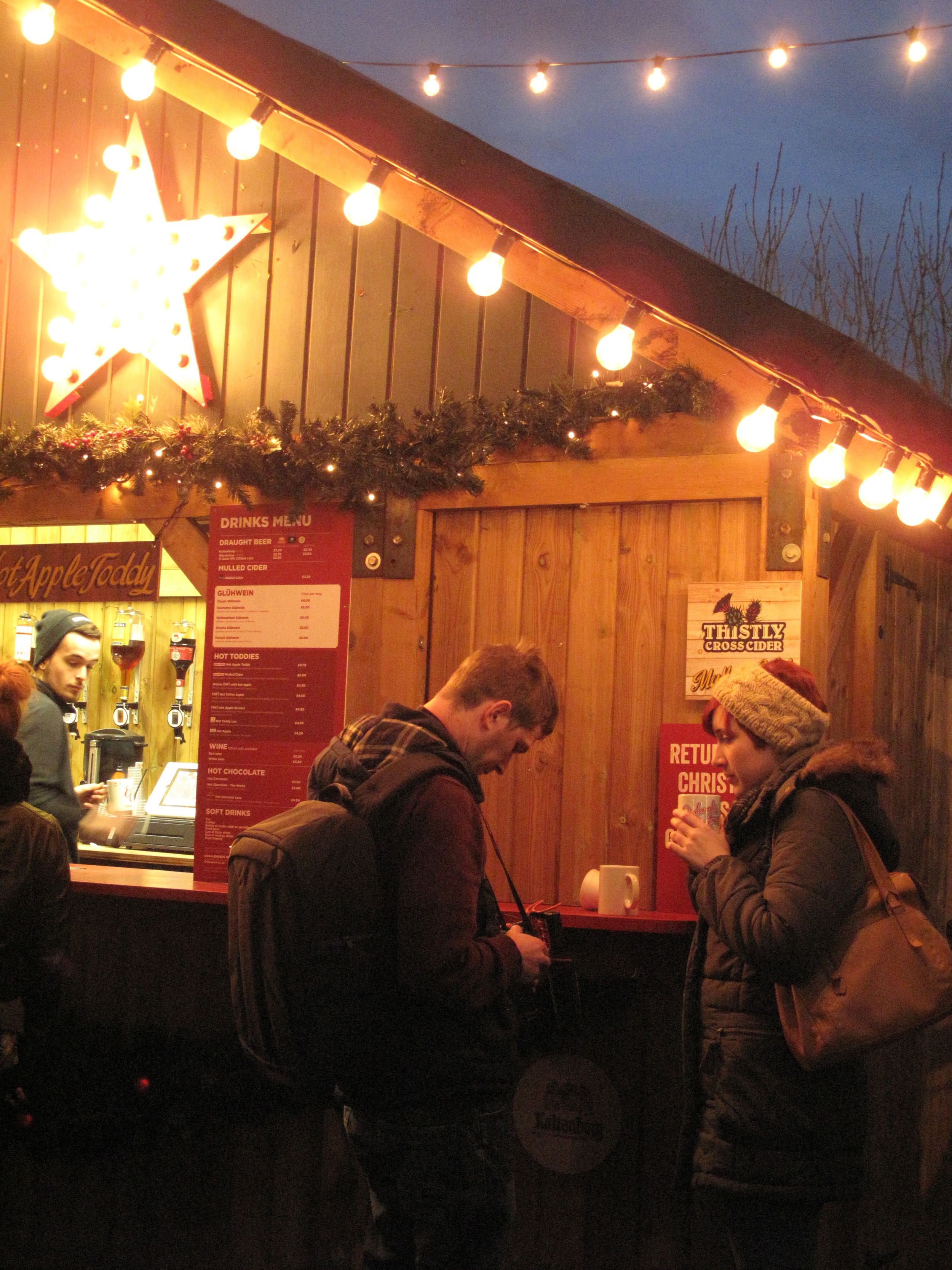 A couple enjoying a hot cider drink at a cart in the Edinburgh Christmas Market.