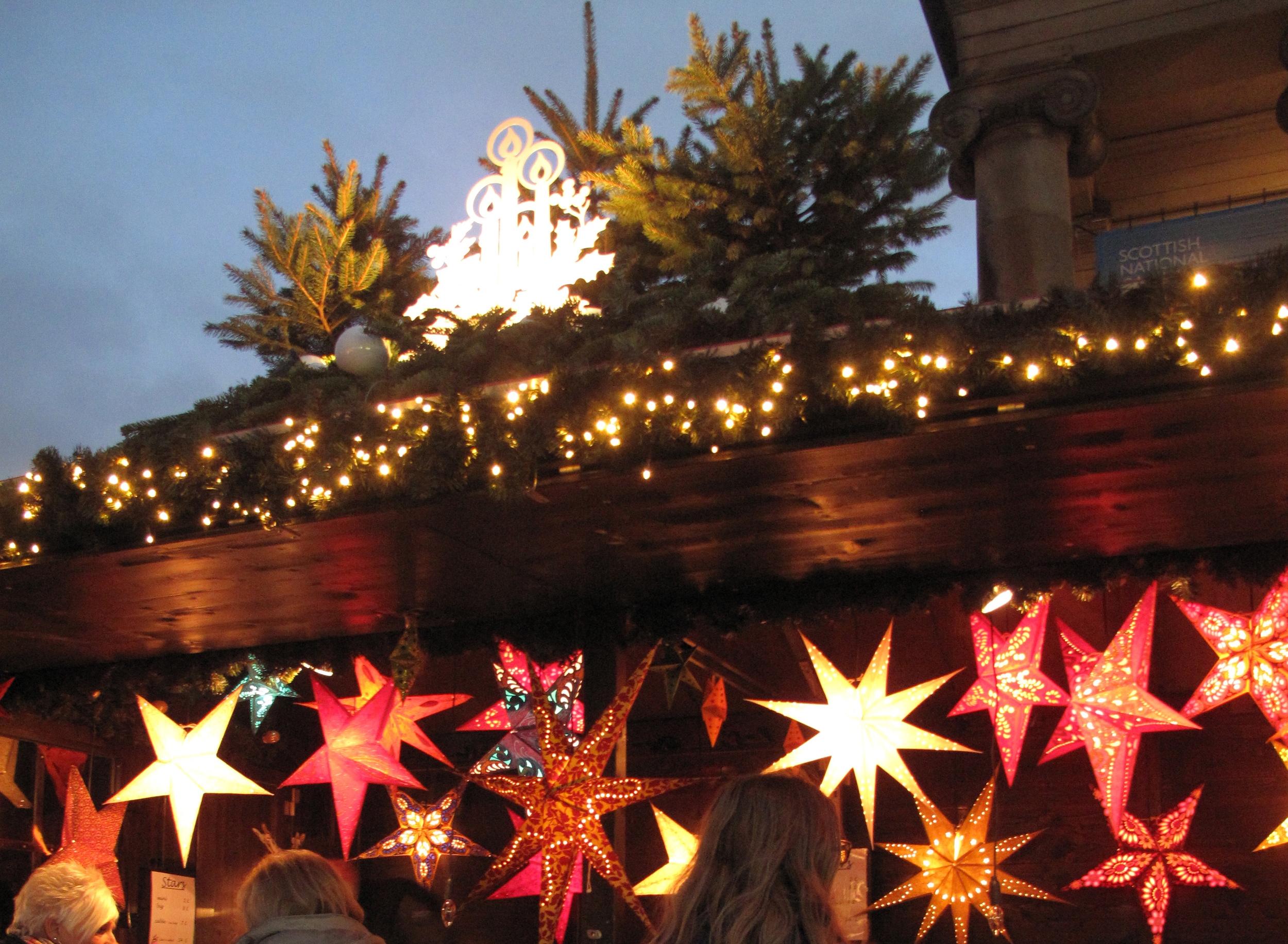 Star lanterns at the Edinburgh Christmas market, all lit up at night.