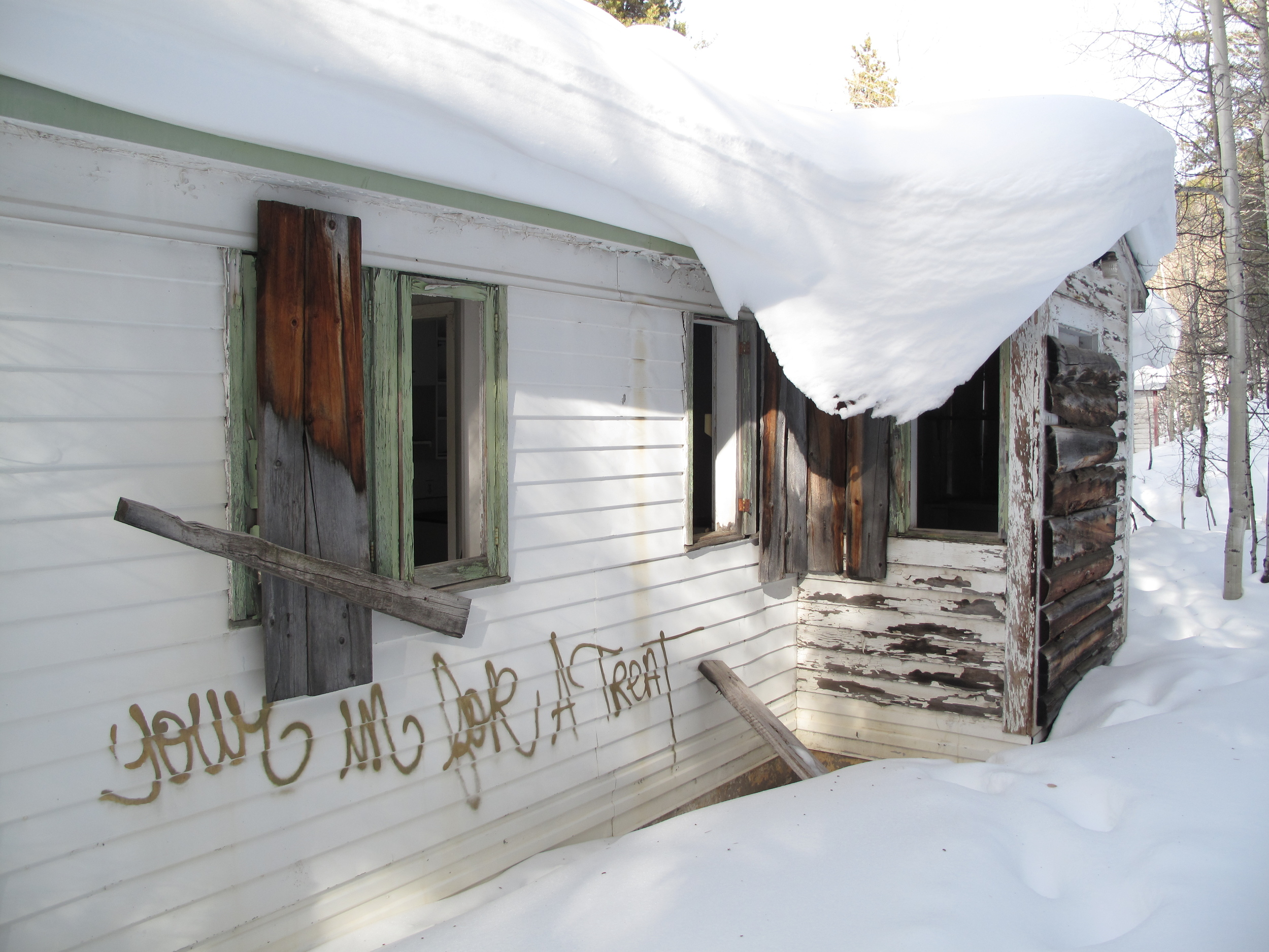 Snow and graffiti covered house, abandoned in the old mining town of Gilman.