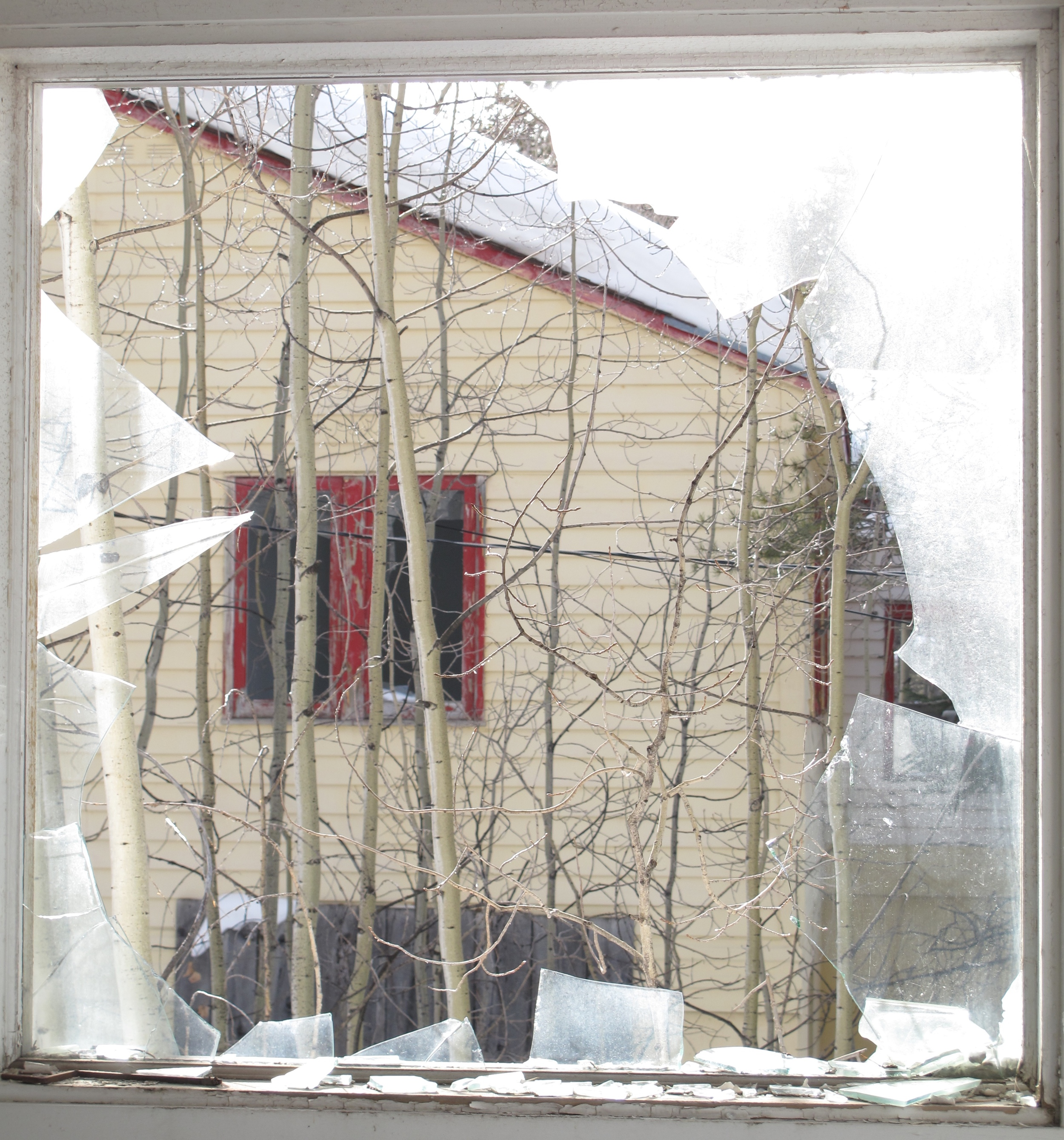 Smashed window, abandoned house in Gilman, CO.