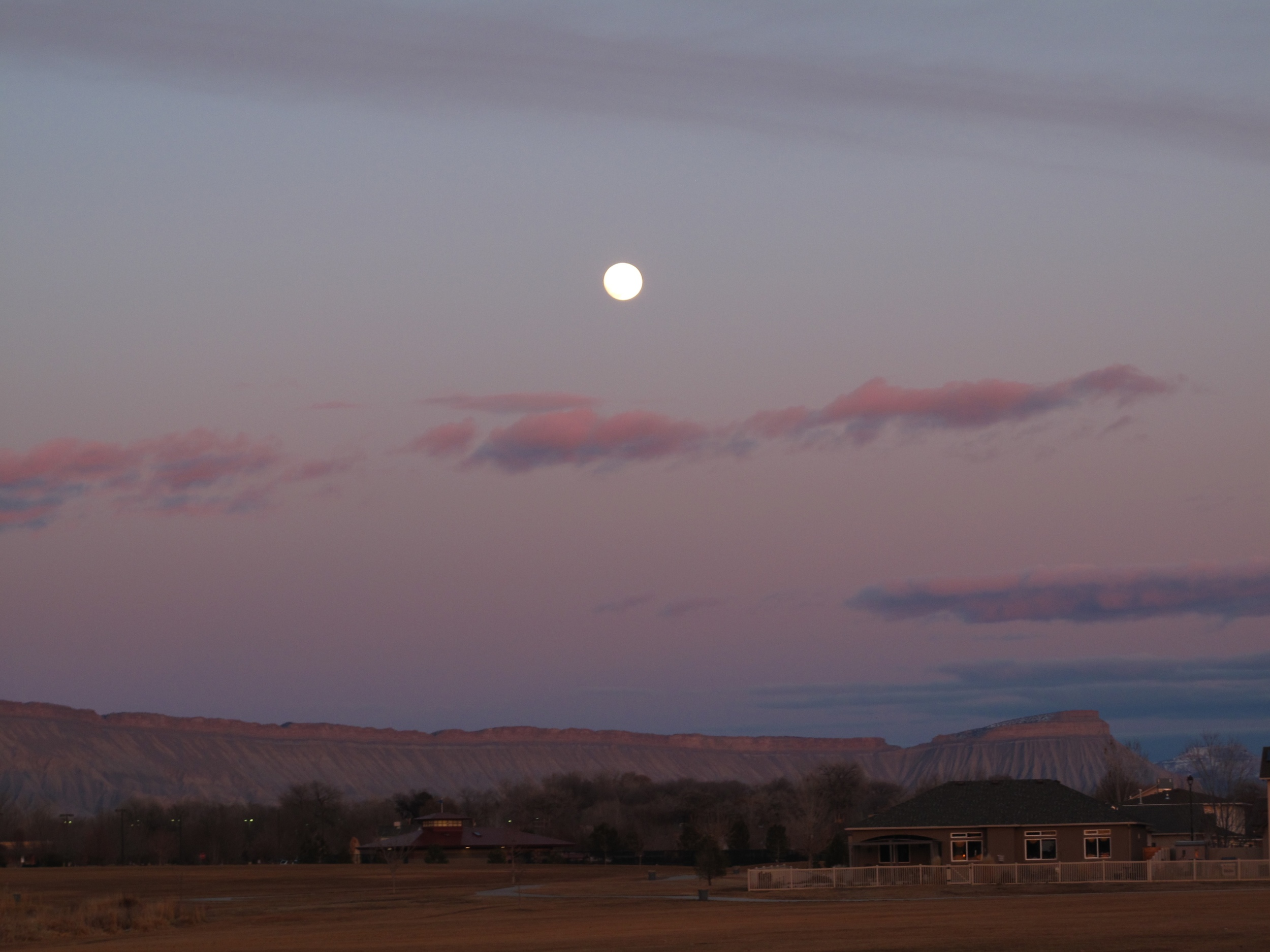 Full moon in a purple sunset over Grand Junctions flat topped mountains.