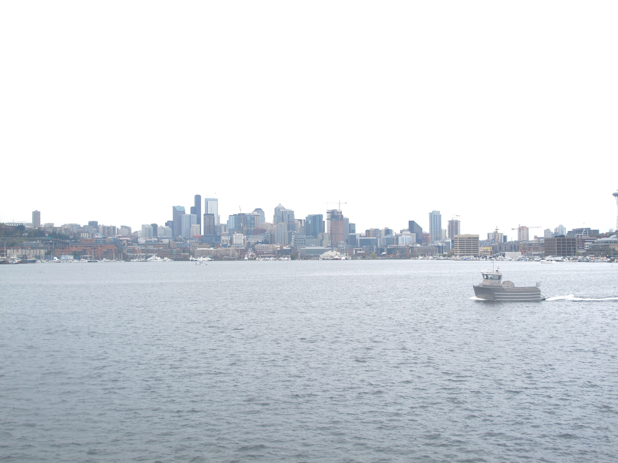 Seattle city skyline seen from Gasworks Park, with a boat driving through.