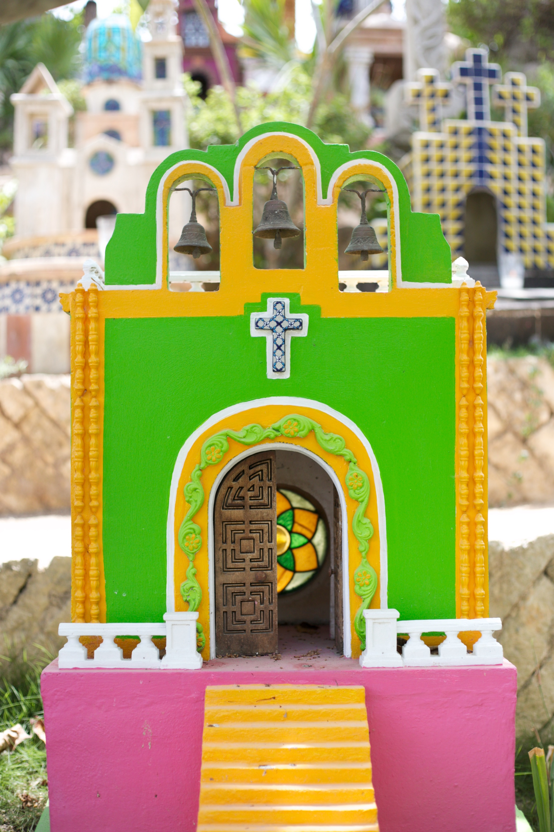A very colourful painted house-like grave marker in a Mexican cemetery.