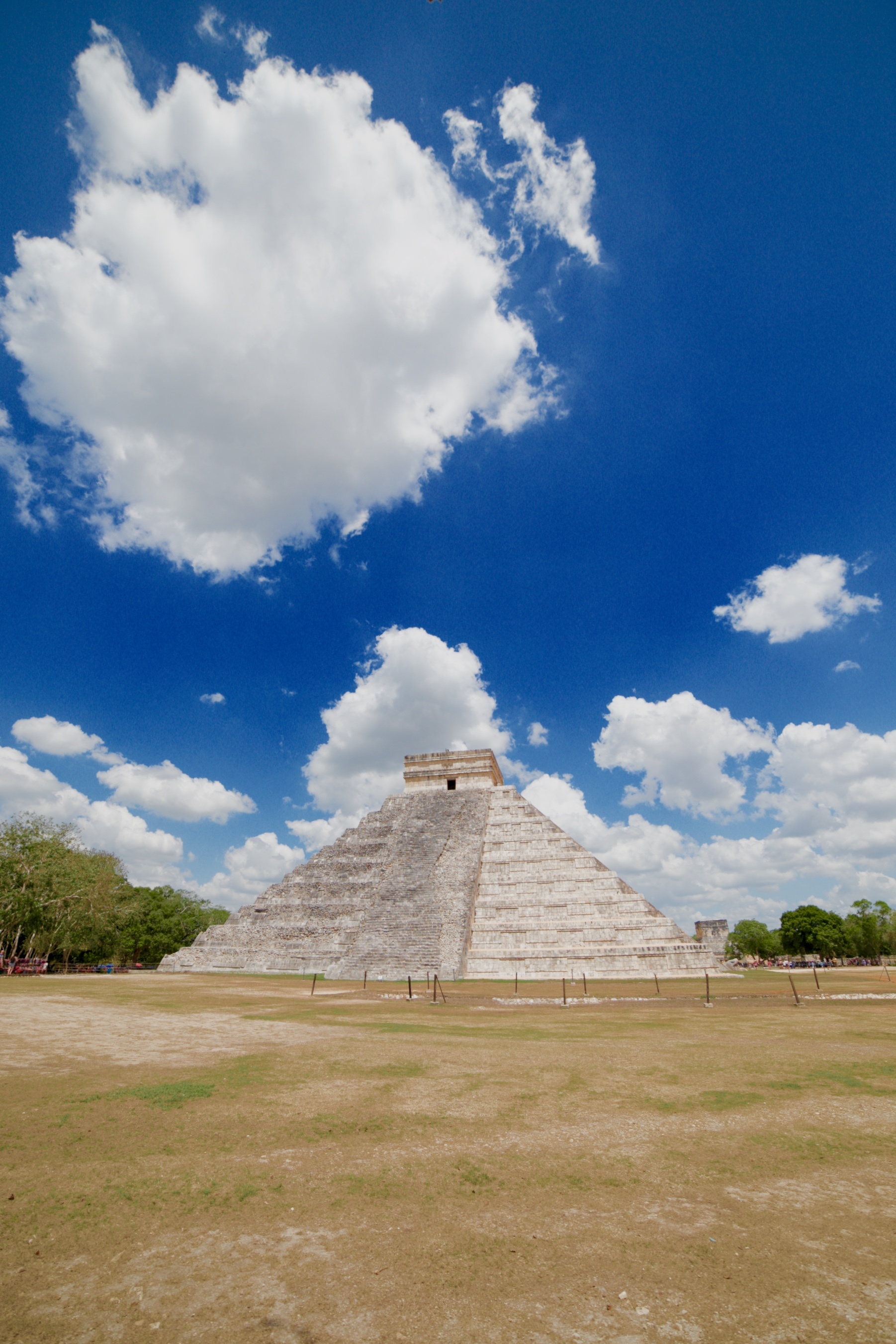 Chichen Itza Mayan ruins professional photography - on a sunny summer day under the blue sky and puffy clouds.