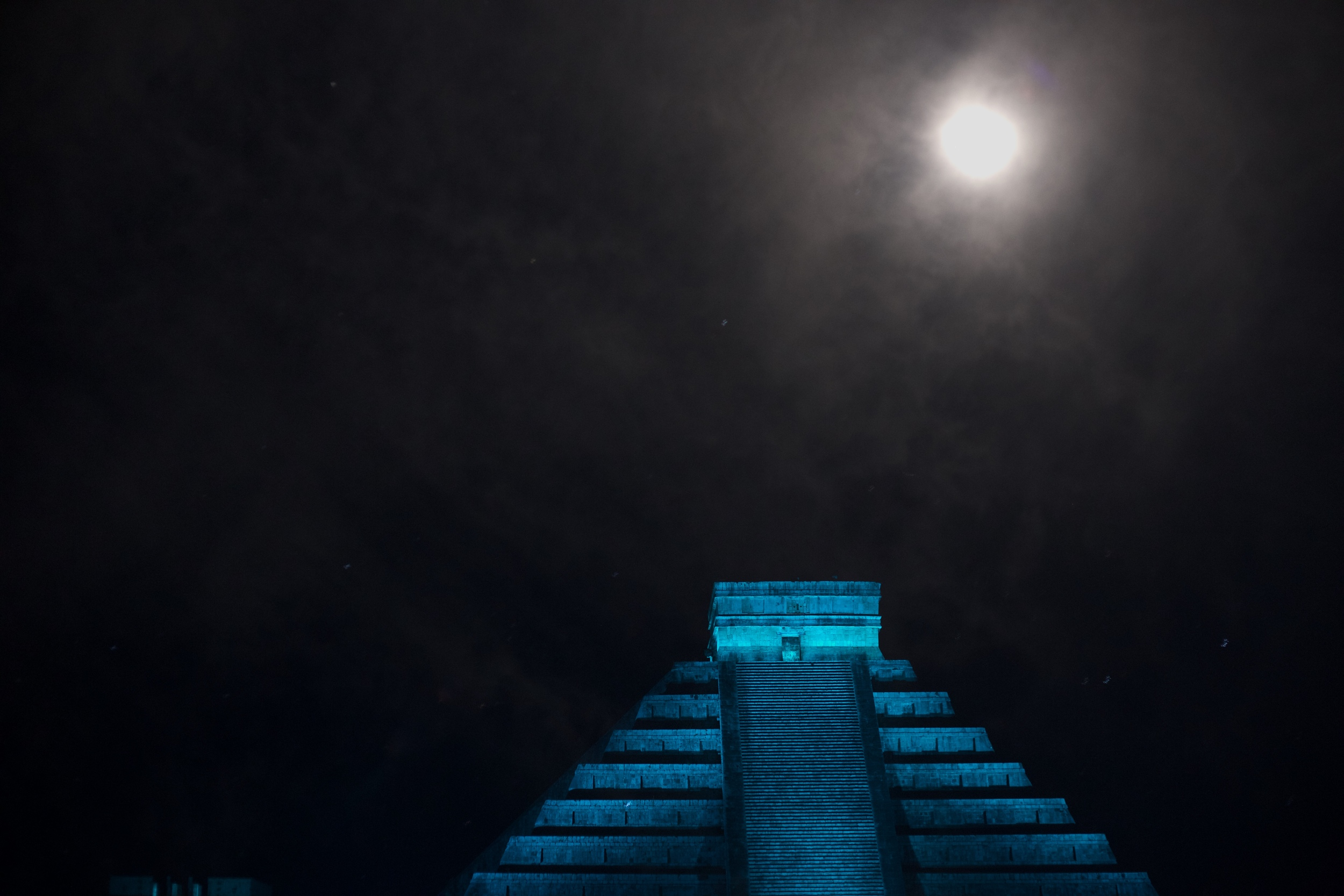 Chichen Itza at night in blue, with a full moon in the background.