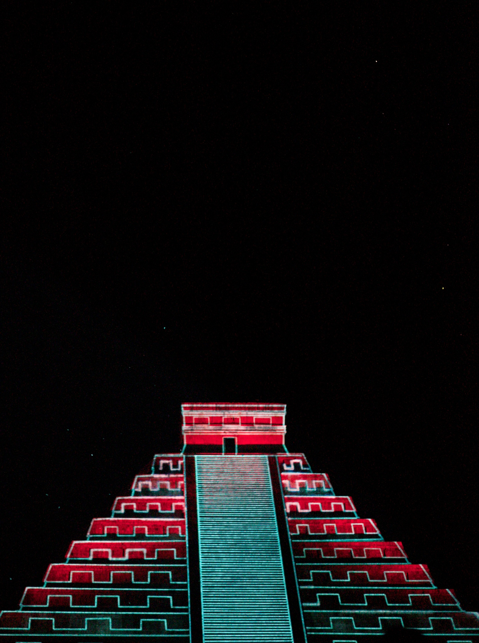 Chichen Itza at night with red lights and mayan patterns.