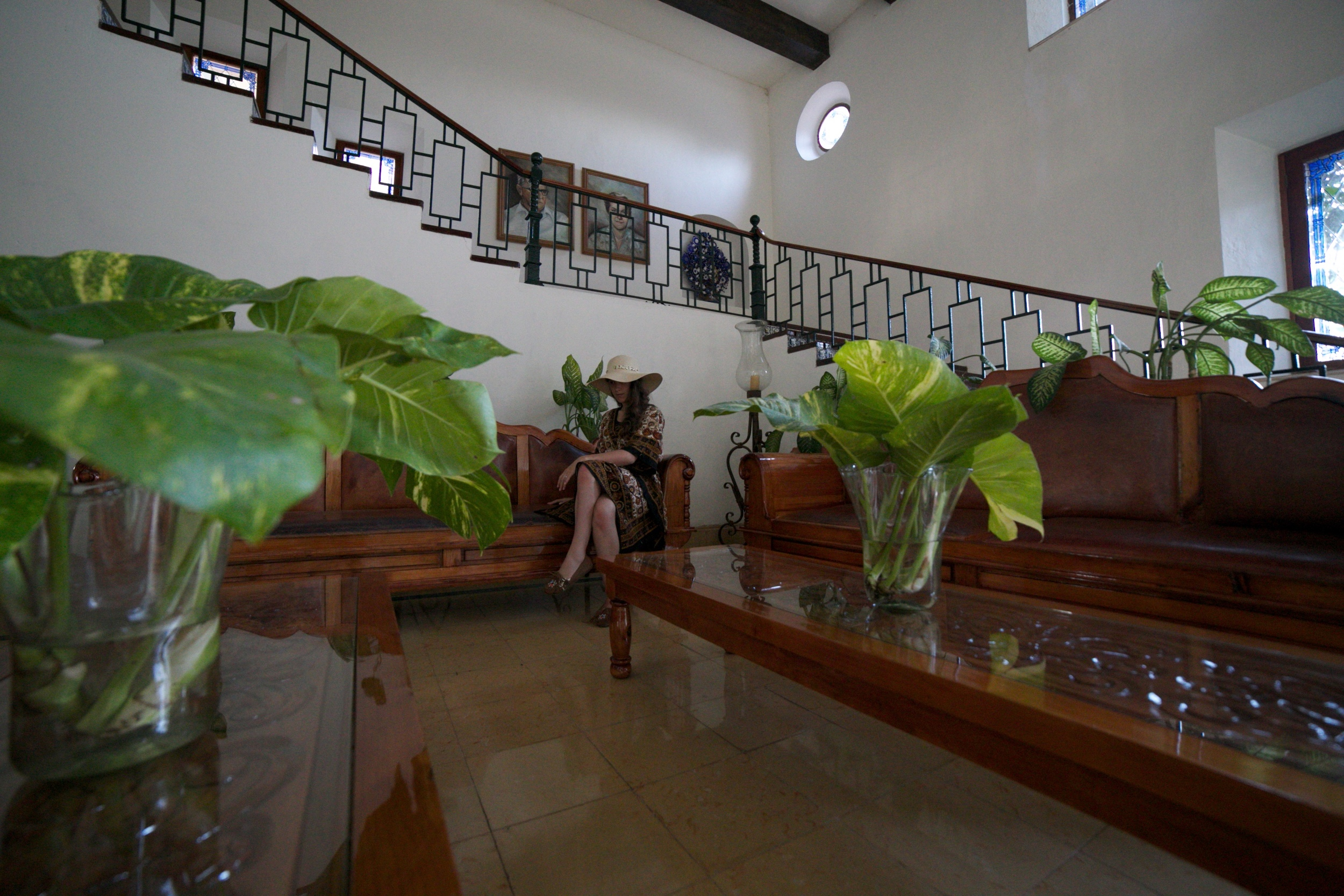Sitting in an old world style lobby at a hotel in Mexico - surrounded by potted plants.