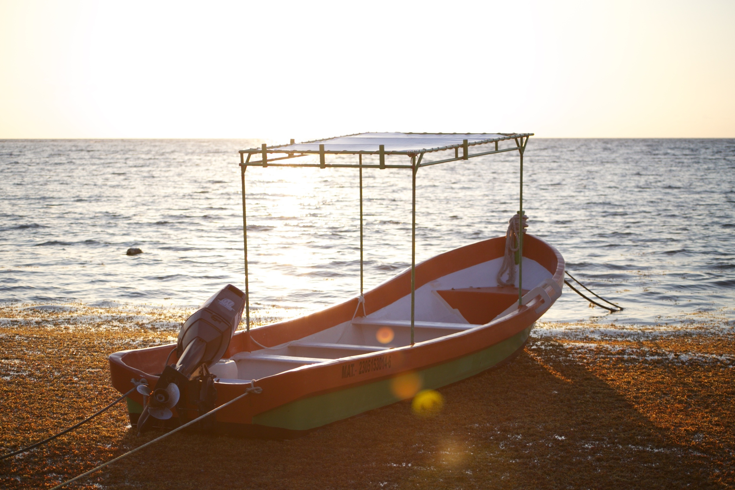 A fishing boat moored in the rays of the rising sun.