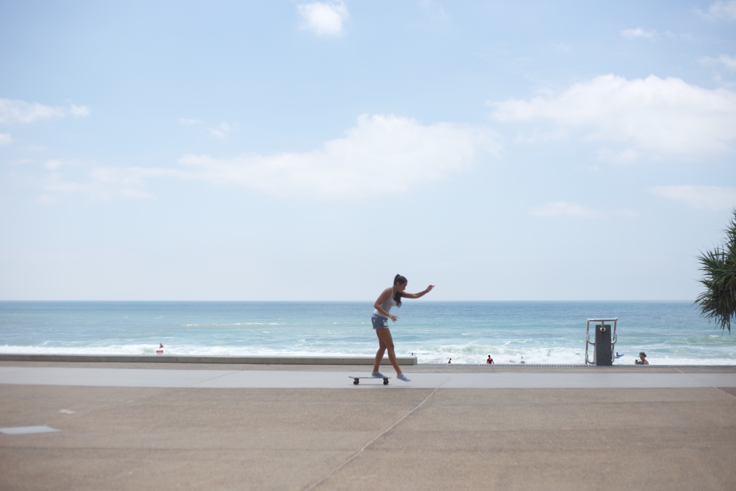 A girl on a long board by the beach in Aussie.