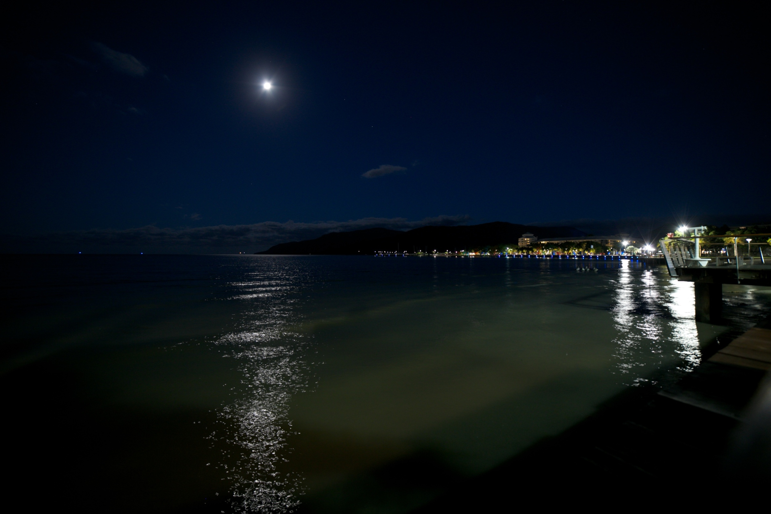 The full moon over Cannes shoreline and city lights.