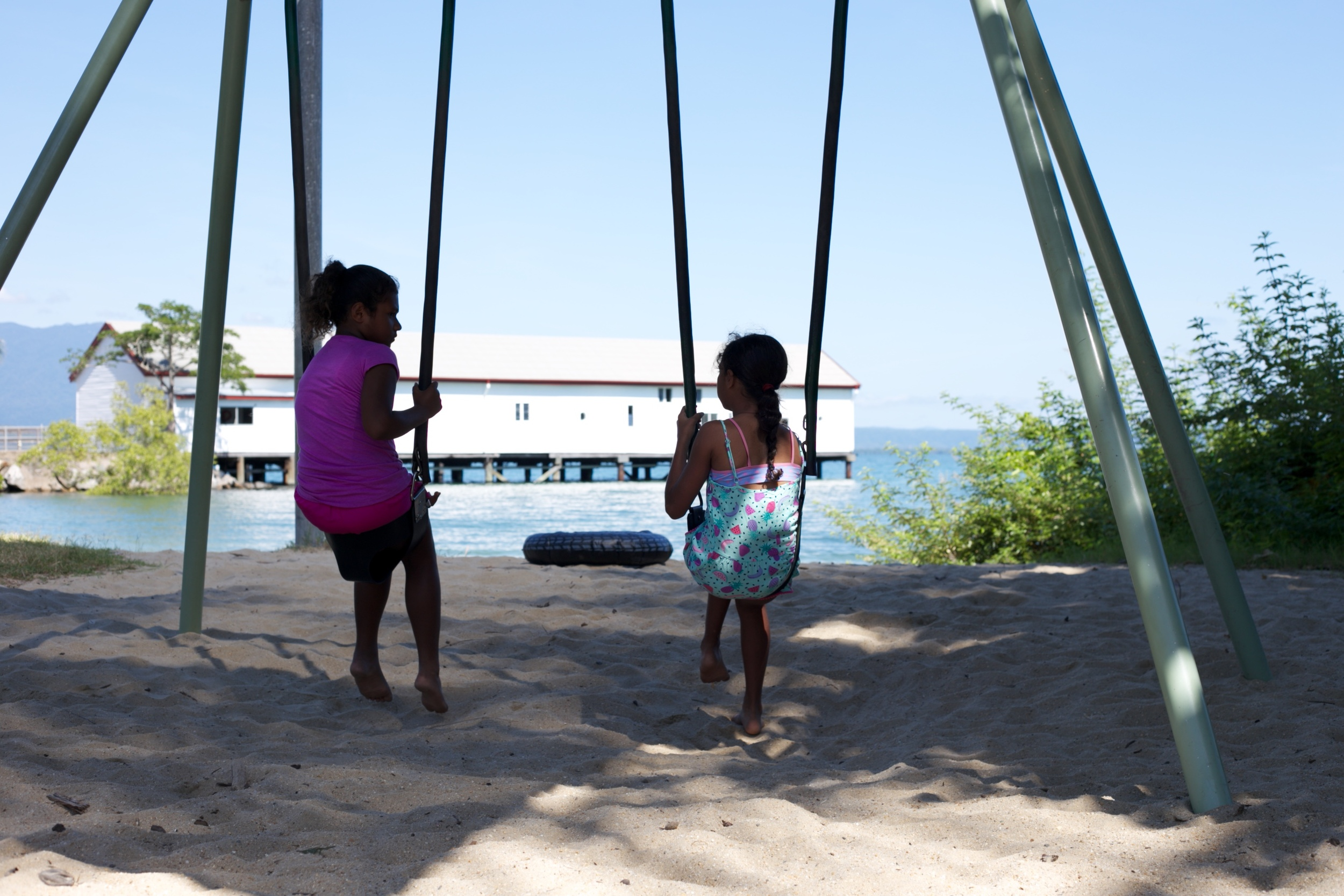 Two young aboriginal girls playing on the swings.
