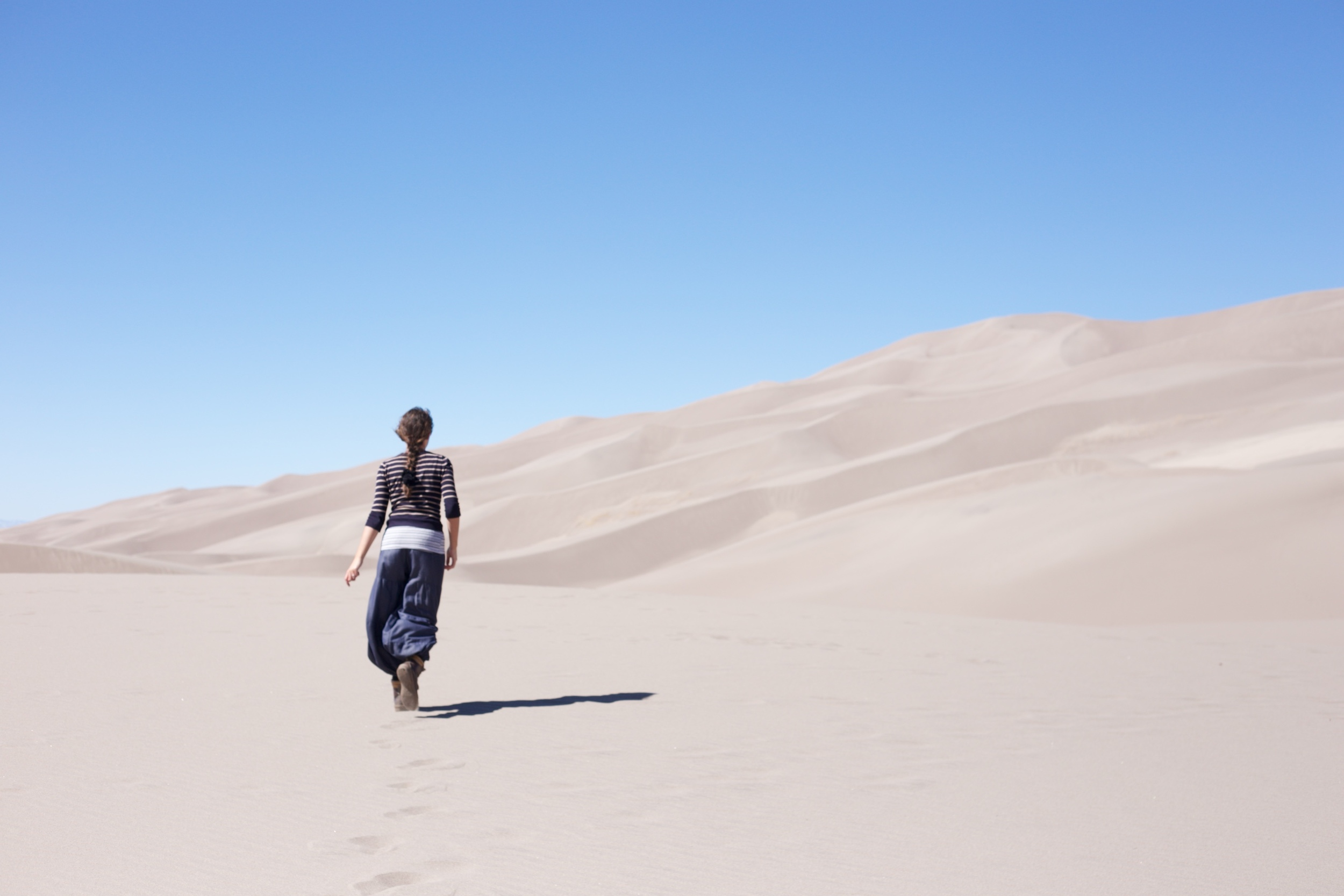 A traveler in the sand dunes of a small desert.