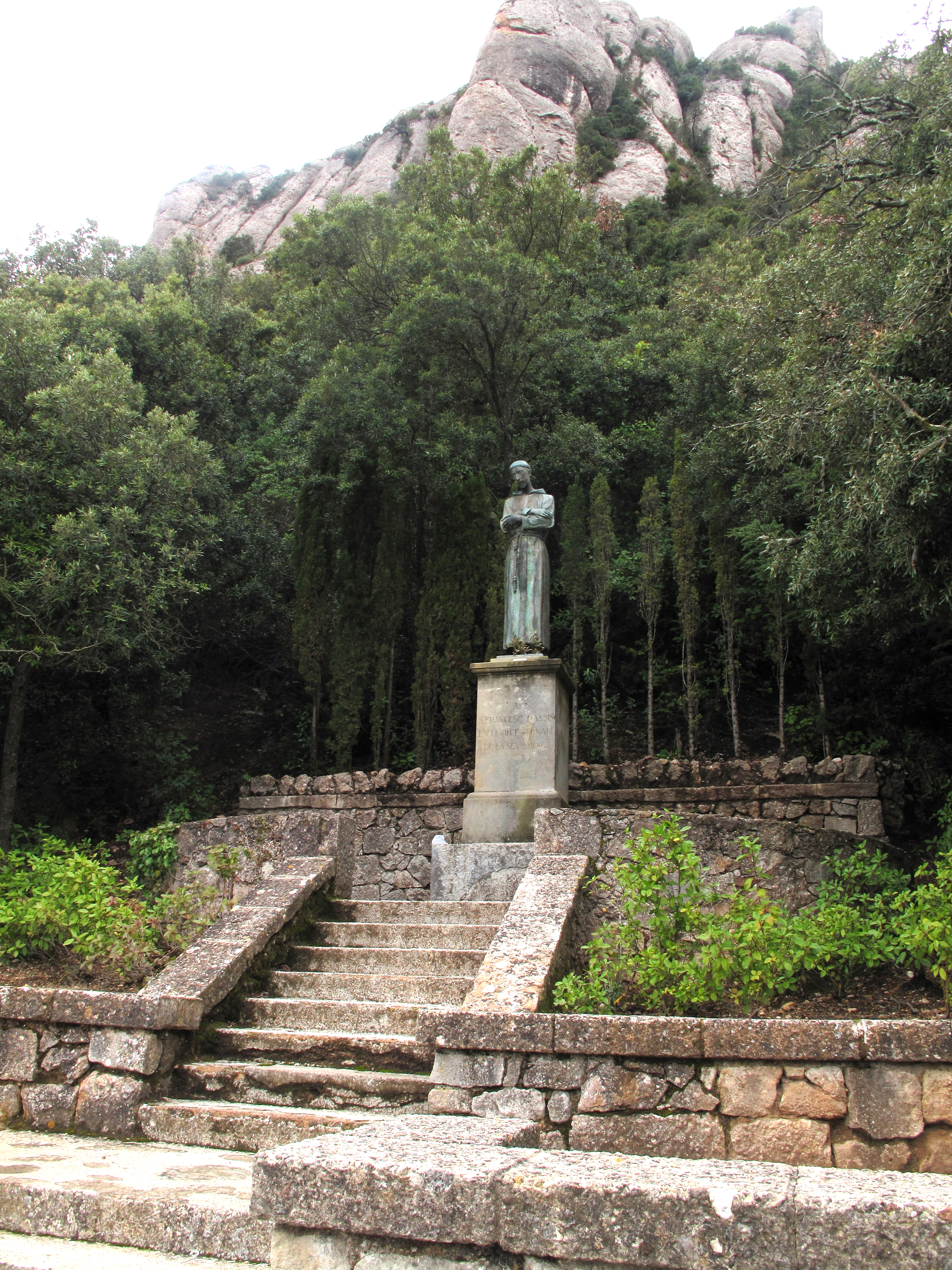 St Francis of Assisi statue hidden in green paths at the monastery on the mountains