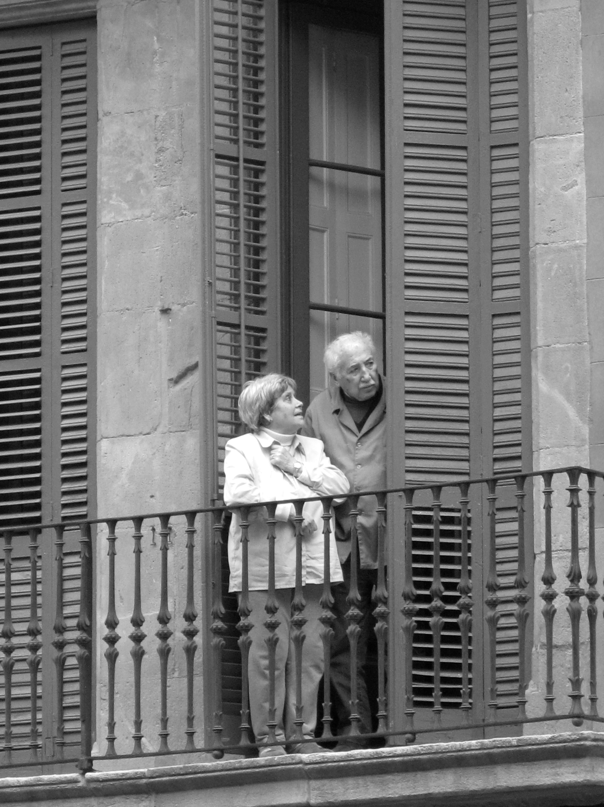 Two old people on a balcony in Barcelona, watching the street performers below.