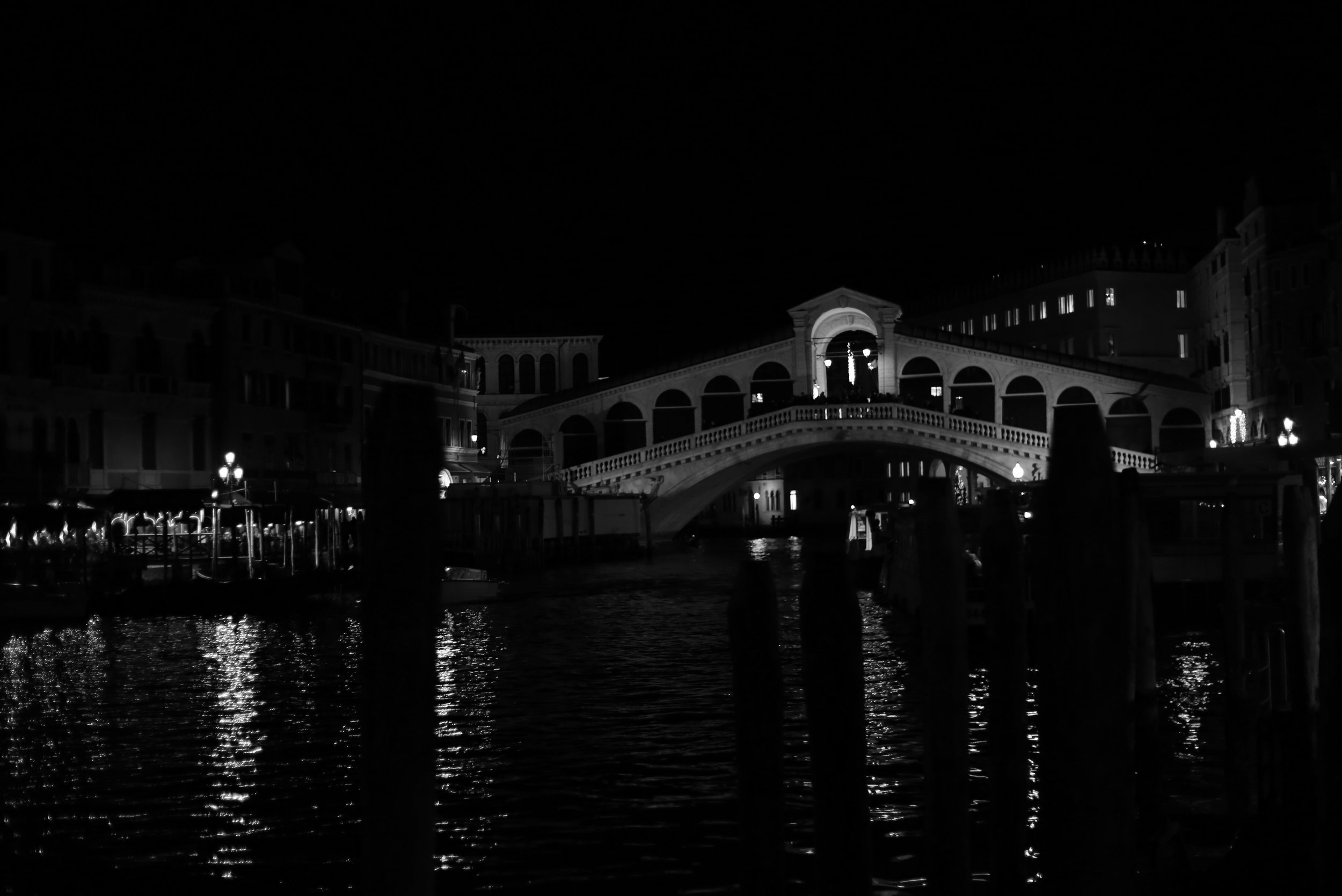 Rialto Bridge is lit up at night and the lights reflect on the water - in black and white.