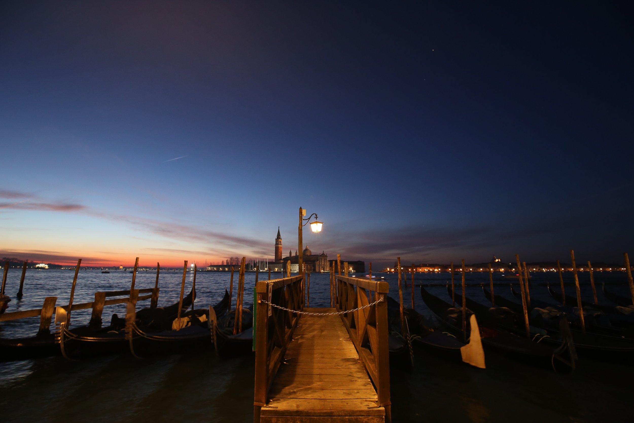Gondolas sway at sunrise, San Giorgio Maggiore is lit up in the background.
