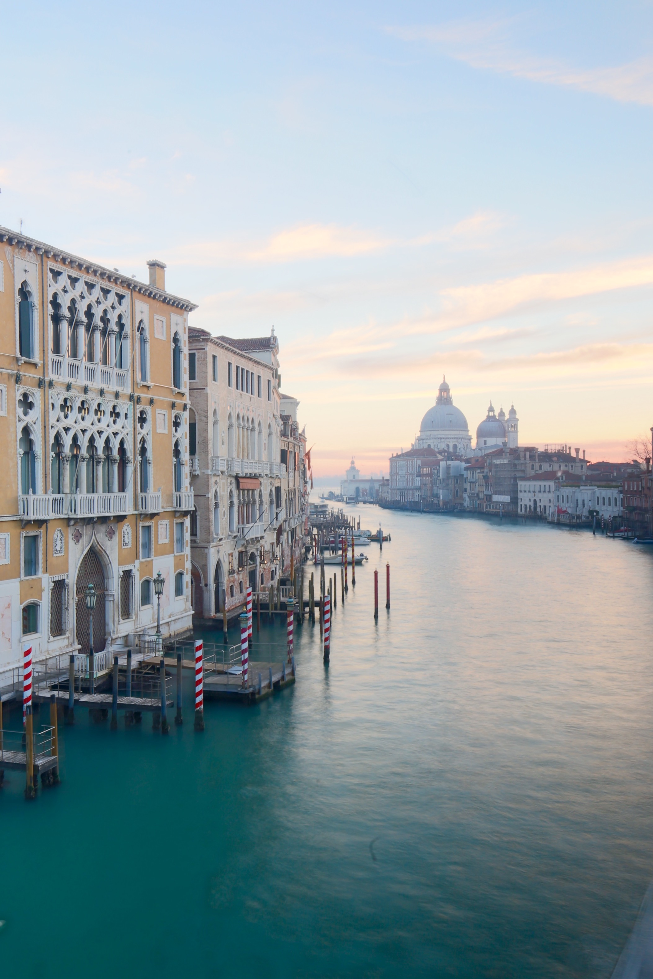 View from the Pont dell'Accademia in the morning in Venice - soft pastel light and blue water.