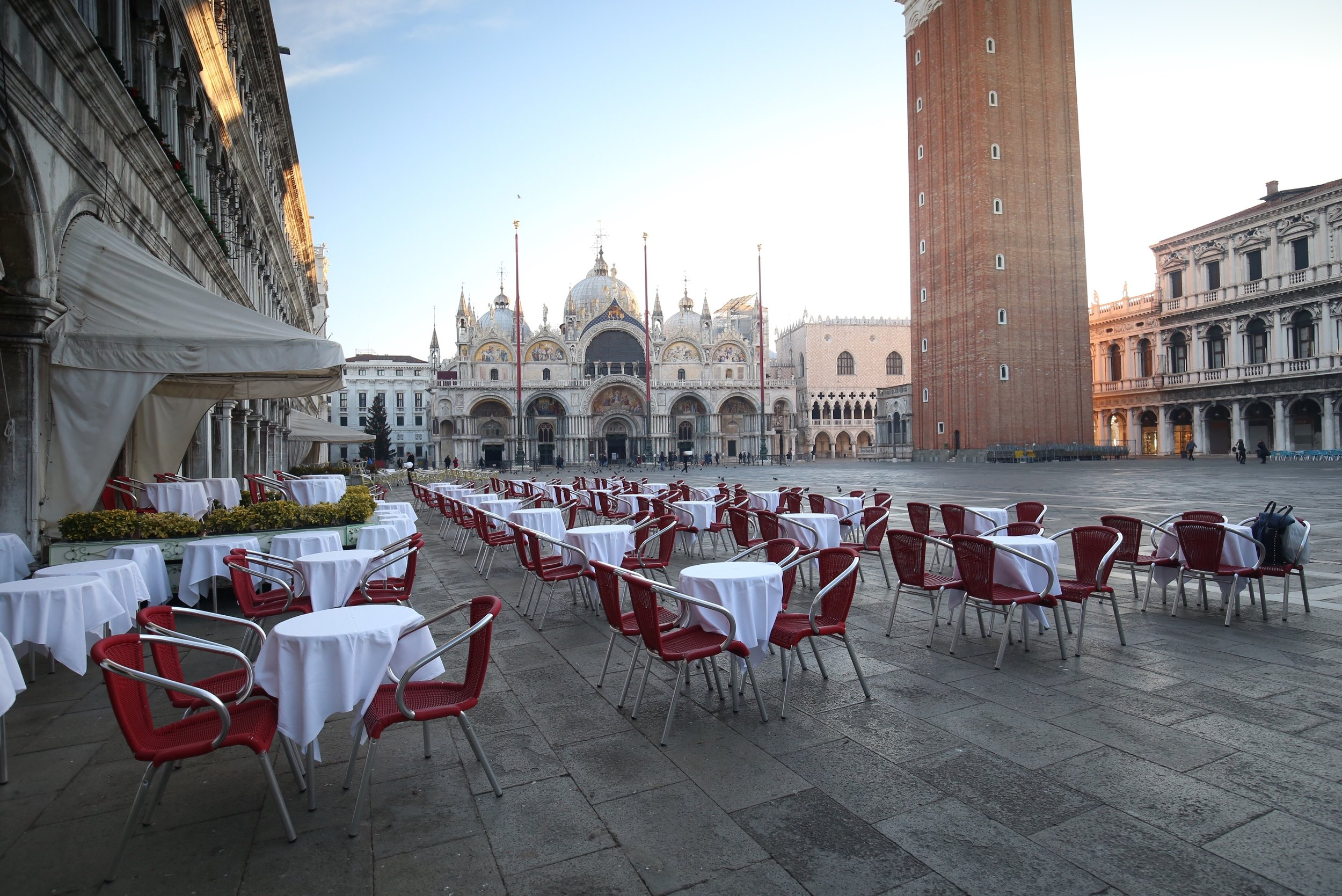 Red seats and small tables ready in the early morning outside St Mark's Basilica.